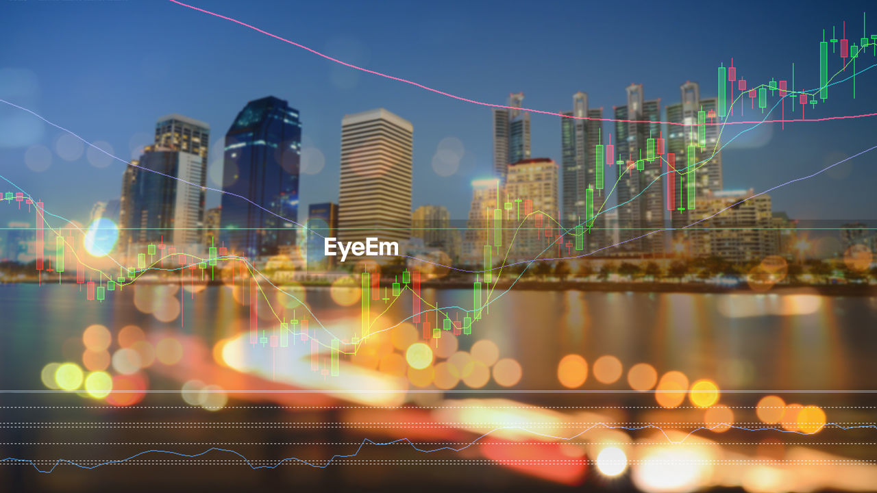 Digital composite image of graph with illuminated buildings in city at night