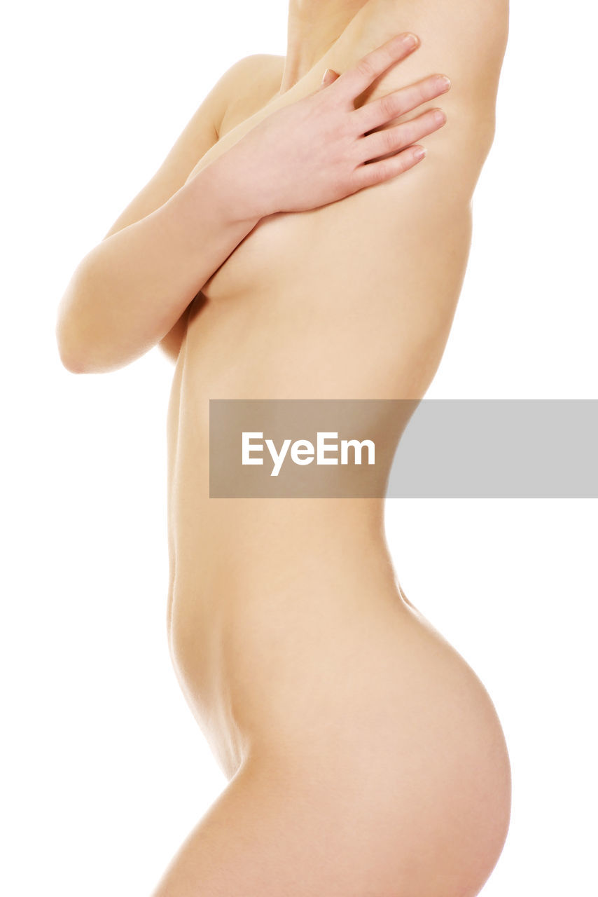 Midsection of naked woman standing against white background