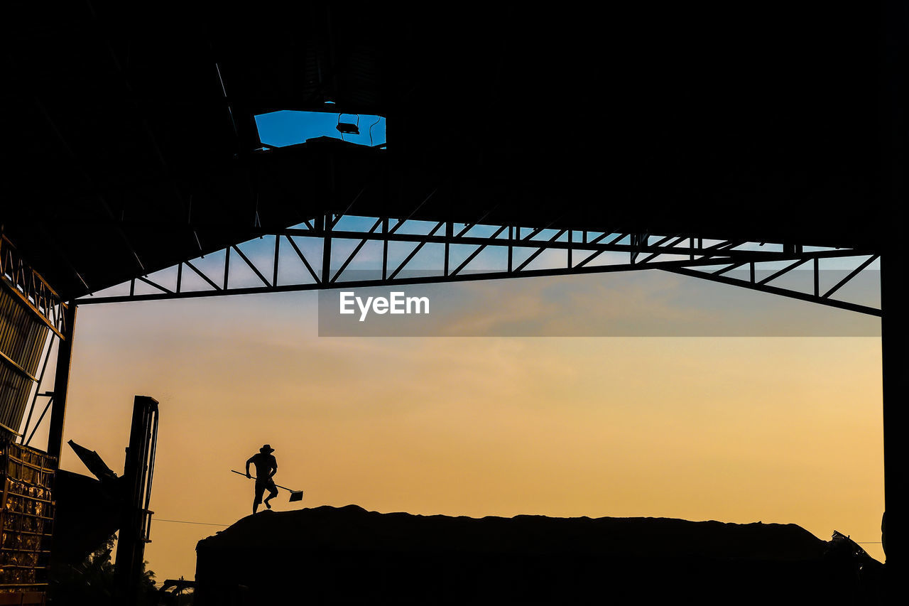 sky, silhouette, sunset, architecture, real people, built structure, one person, men, nature, lifestyles, low angle view, leisure activity, orange color, unrecognizable person, bridge, outdoors, connection, beauty in nature, cloud - sky