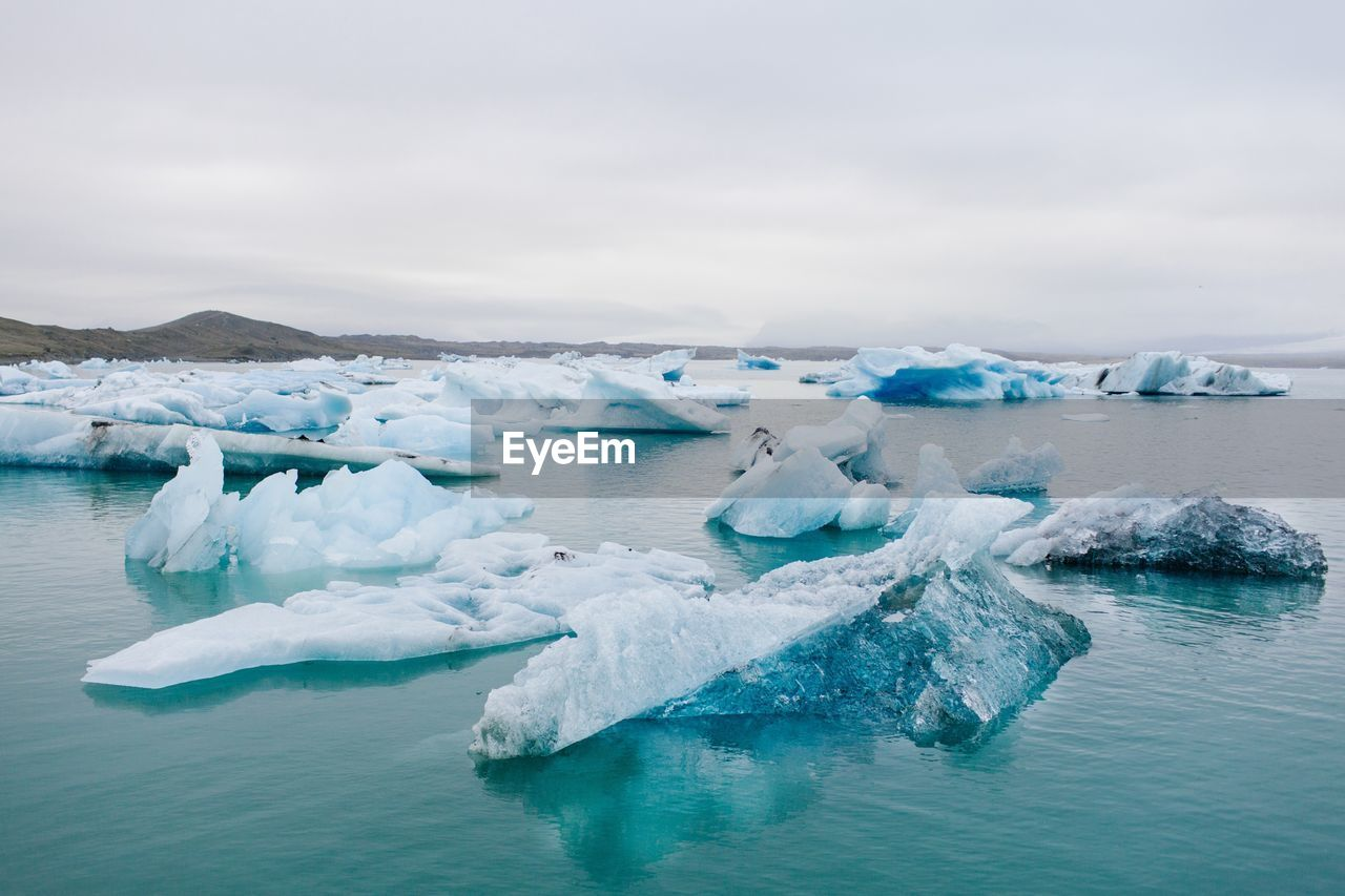 PANORAMIC SHOT OF ICE FLOATING ON SEA AGAINST SKY
