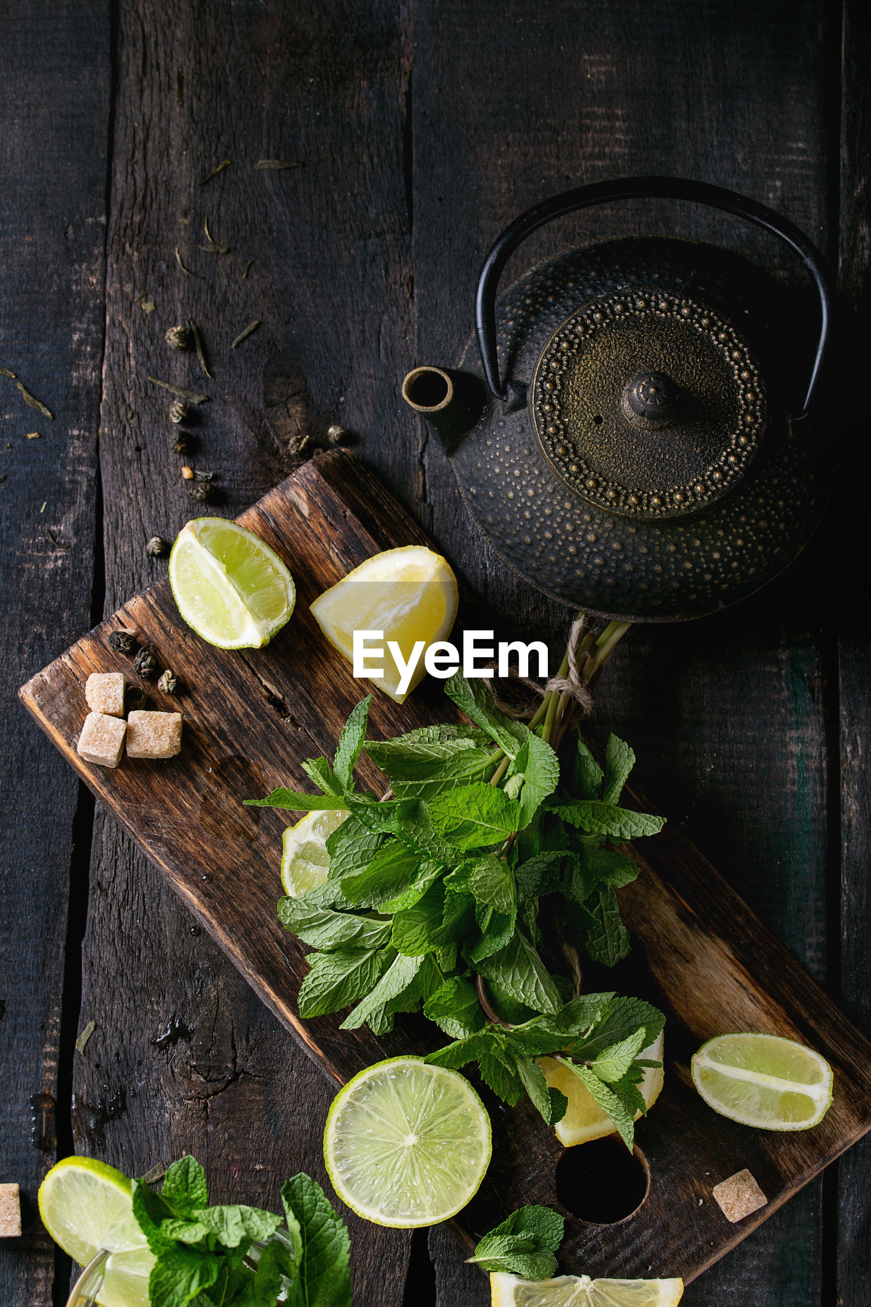 High angle view of lemons and mint leaves on cutting board