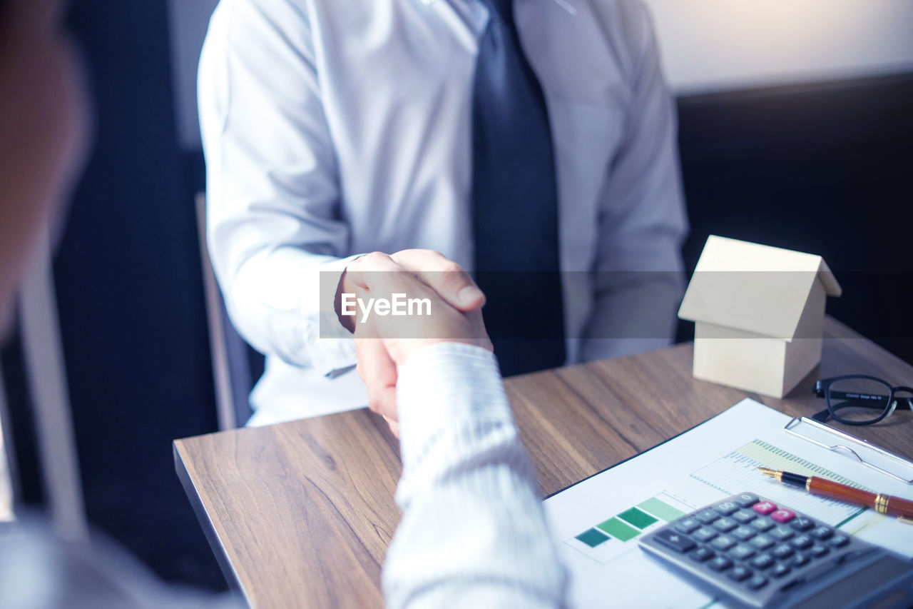 midsection, business, office, business person, men, table, businessman, real people, indoors, professional occupation, males, adult, occupation, people, technology, selective focus, furniture, cooperation, calculator, corporate business