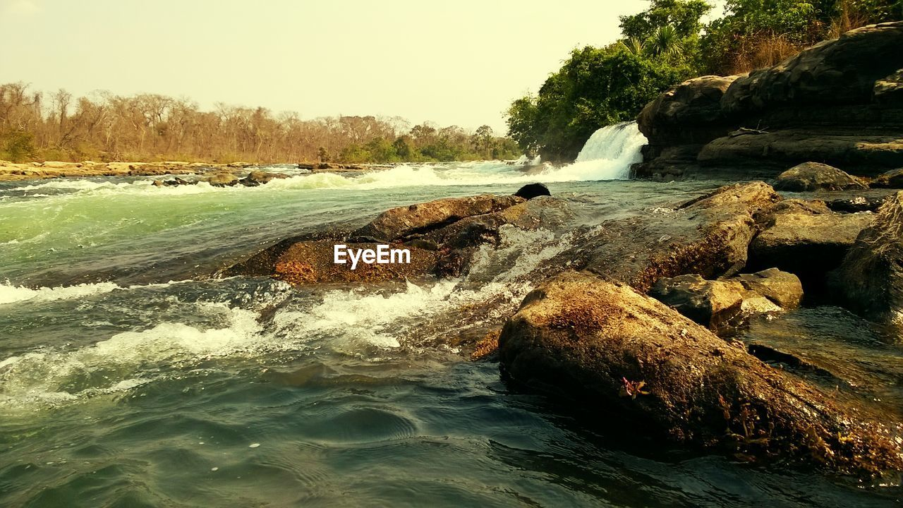 water, rock - object, motion, beauty in nature, nature, scenics, sea, waterfront, outdoors, day, no people, tranquil scene, tranquility, power in nature, clear sky, wave, waterfall, tree, sky