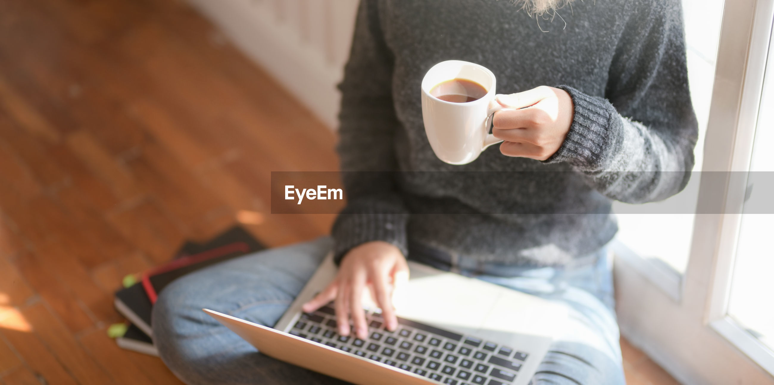 Low section of woman drinking coffee while using laptop while sitting at home