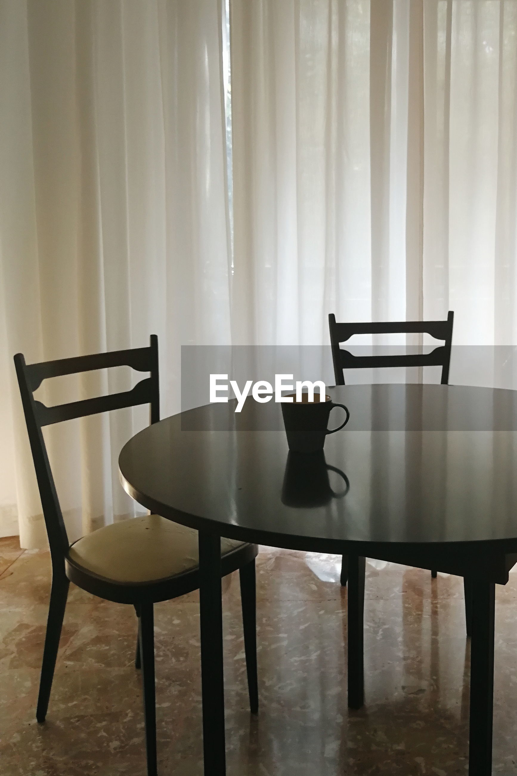 Empty chairs and table with cup against curtain at home
