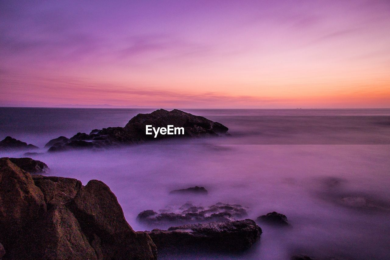 Scenic view of rocks on sea during sunset