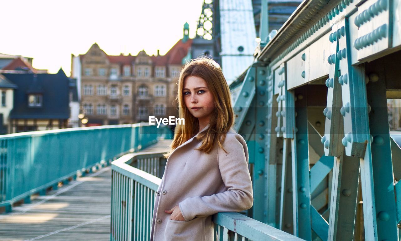 Portrait of beautiful young woman standing by railing on bridge
