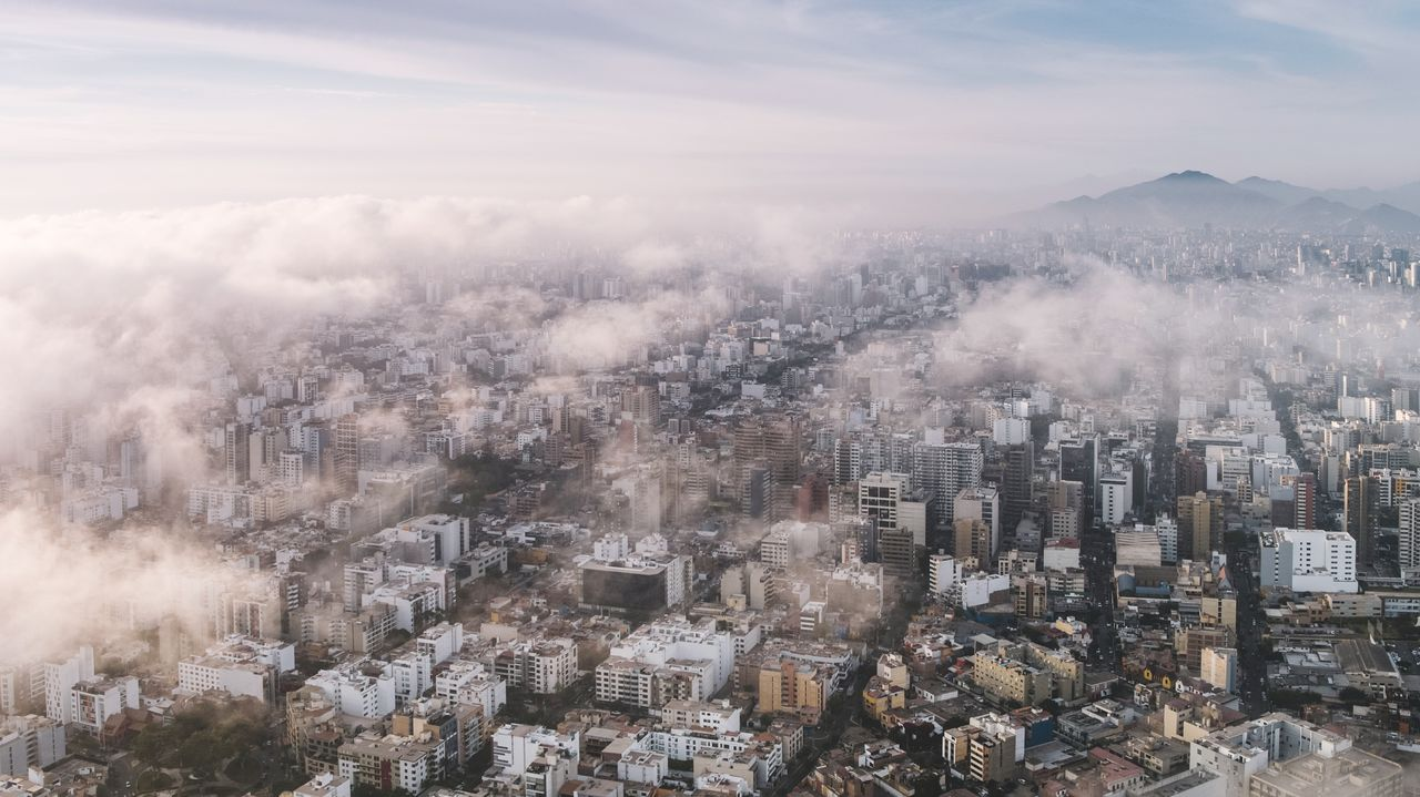 building exterior, architecture, sky, built structure, city, cityscape, building, residential district, no people, cloud - sky, nature, day, fog, high angle view, outdoors, aerial view, smoke - physical structure, mountain, office building exterior, pollution, skyscraper, air pollution, townscape