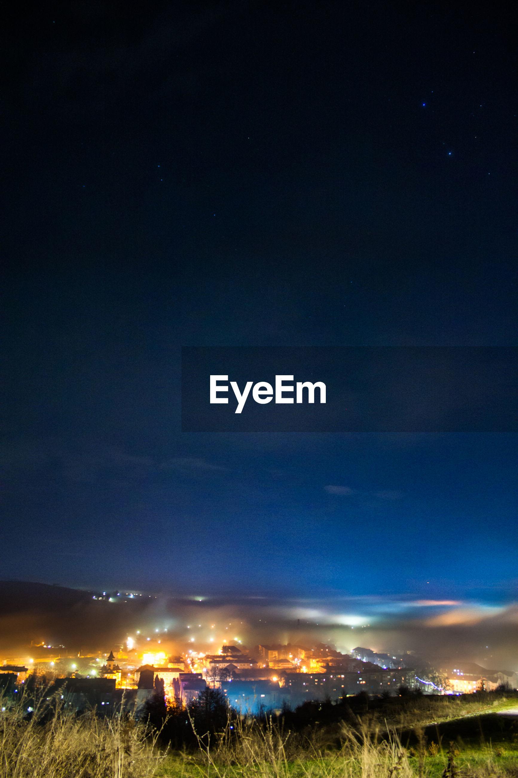 Illuminated city against clear sky at night