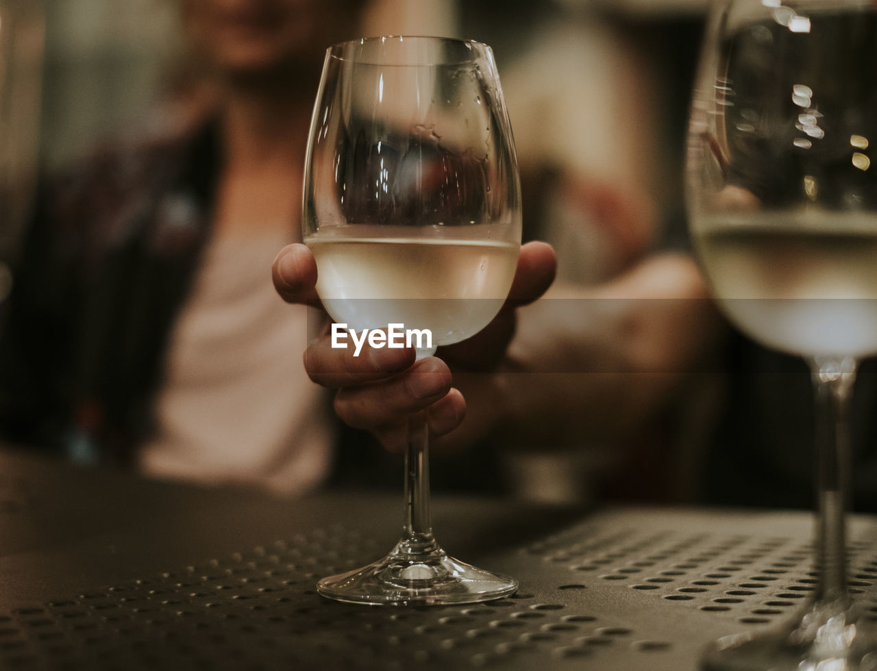 Close-up of hand holding wineglass at table