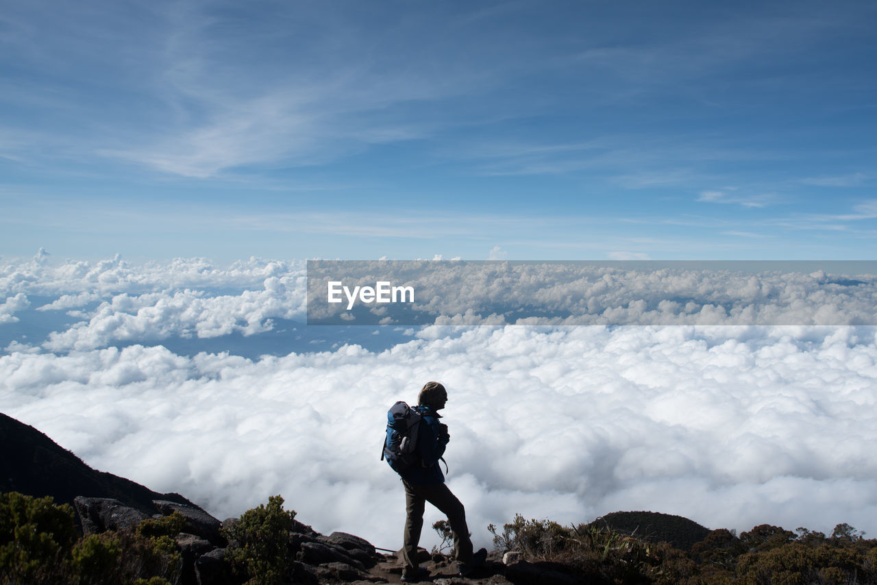 Hiker Standing On Mountain Against Cloudscape