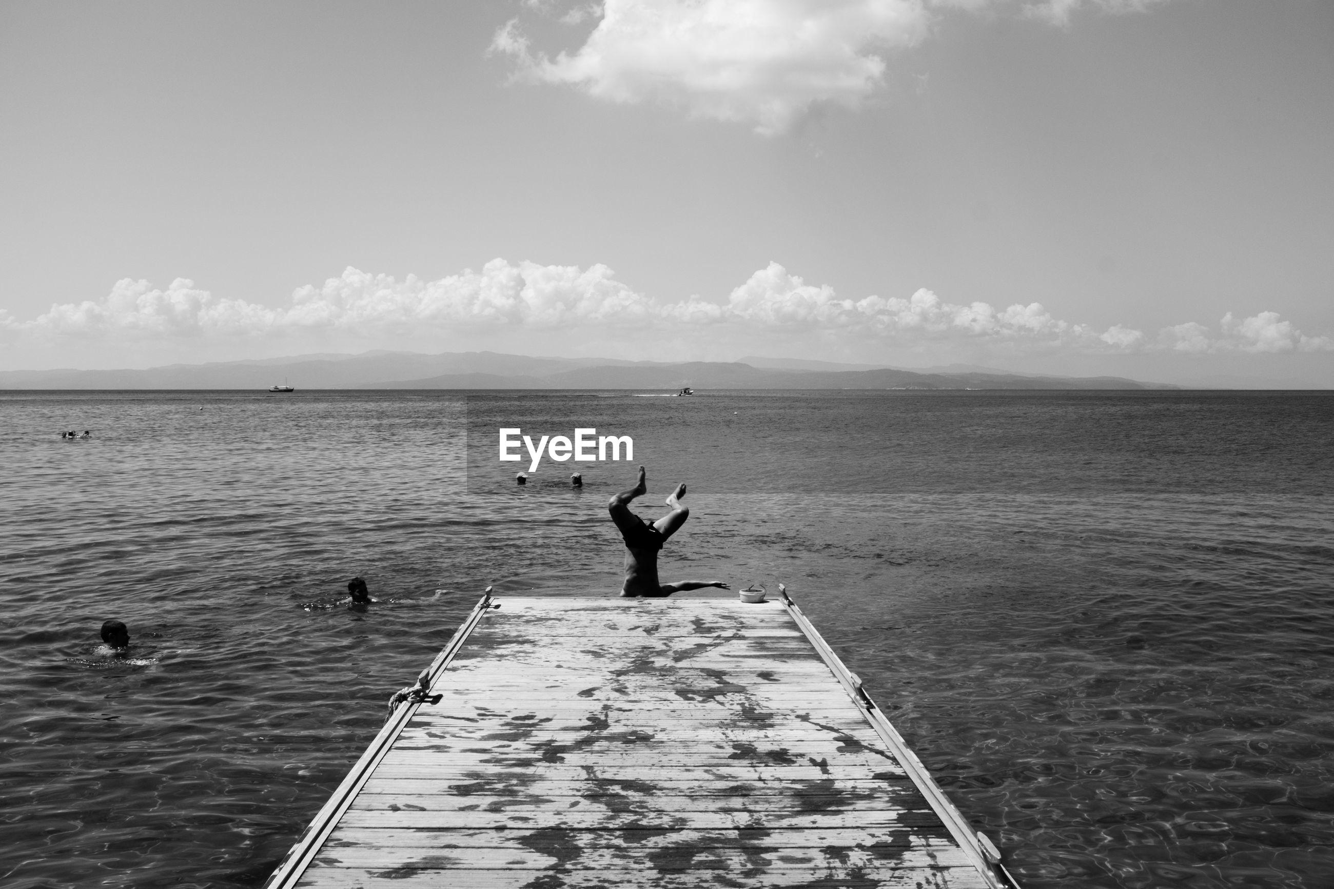MAN STANDING ON SEA AGAINST SKY