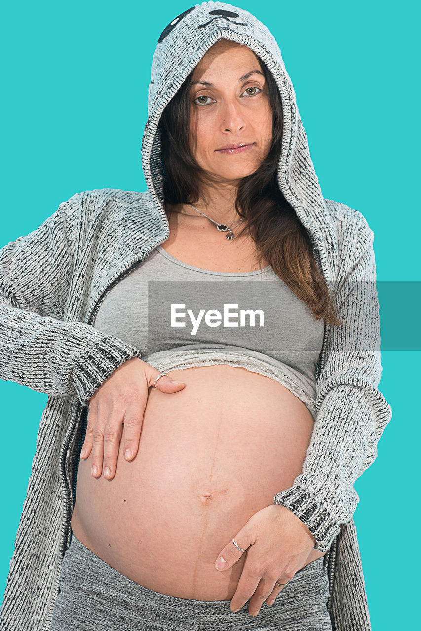 portrait, pregnant, one person, abdomen, looking at camera, real people, studio shot, lifestyles, standing, day, adult, adults only, people