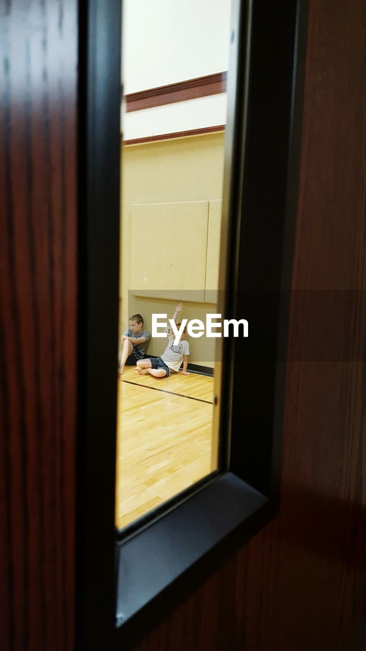 indoors, window, men, door, real people, wood, entrance, boys, two people, hardwood floor, people, males, togetherness, physical education, child, glass - material, sitting, childhood, gym, transparent, flooring, waiting, innocence, exercise class