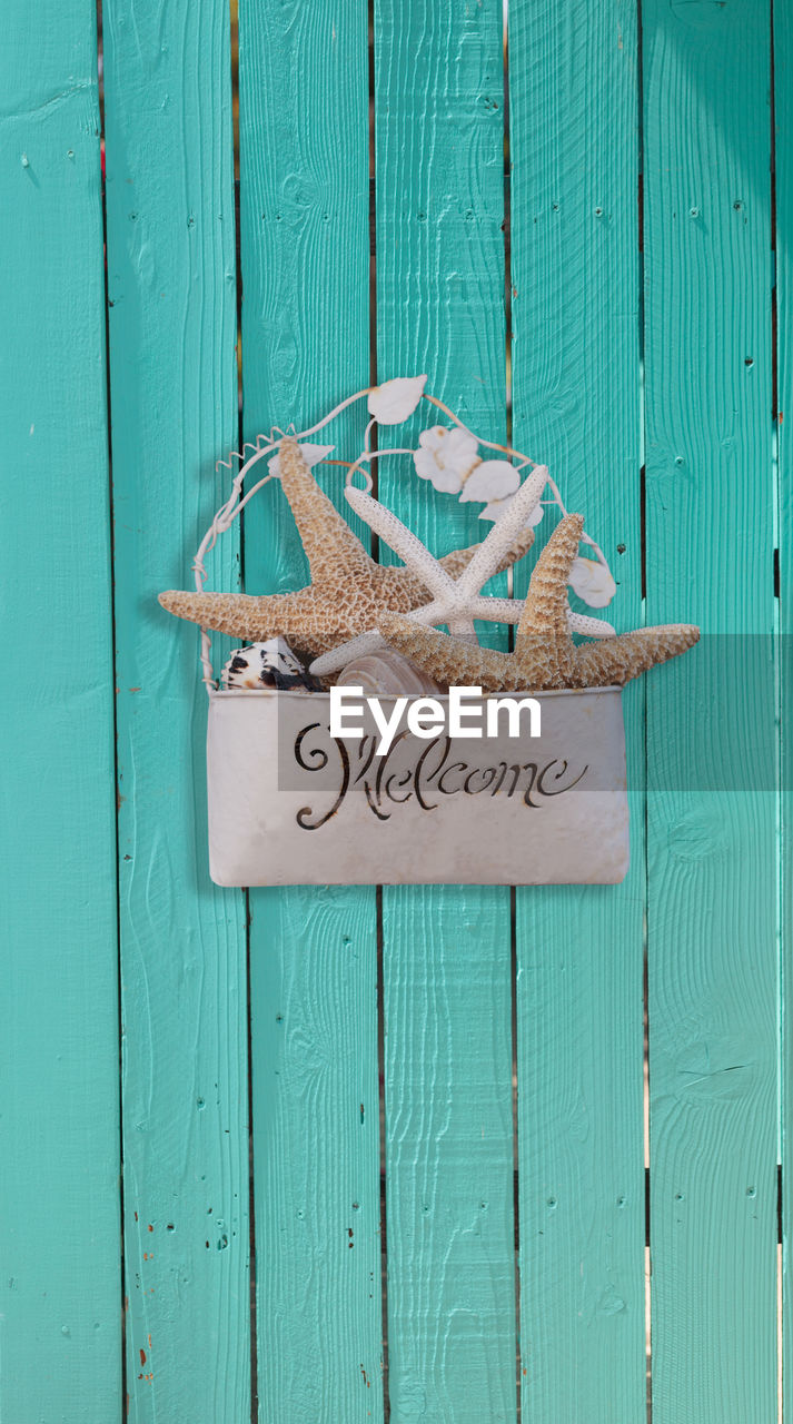 Close-Up Of Welcome Sign On Wooden Door
