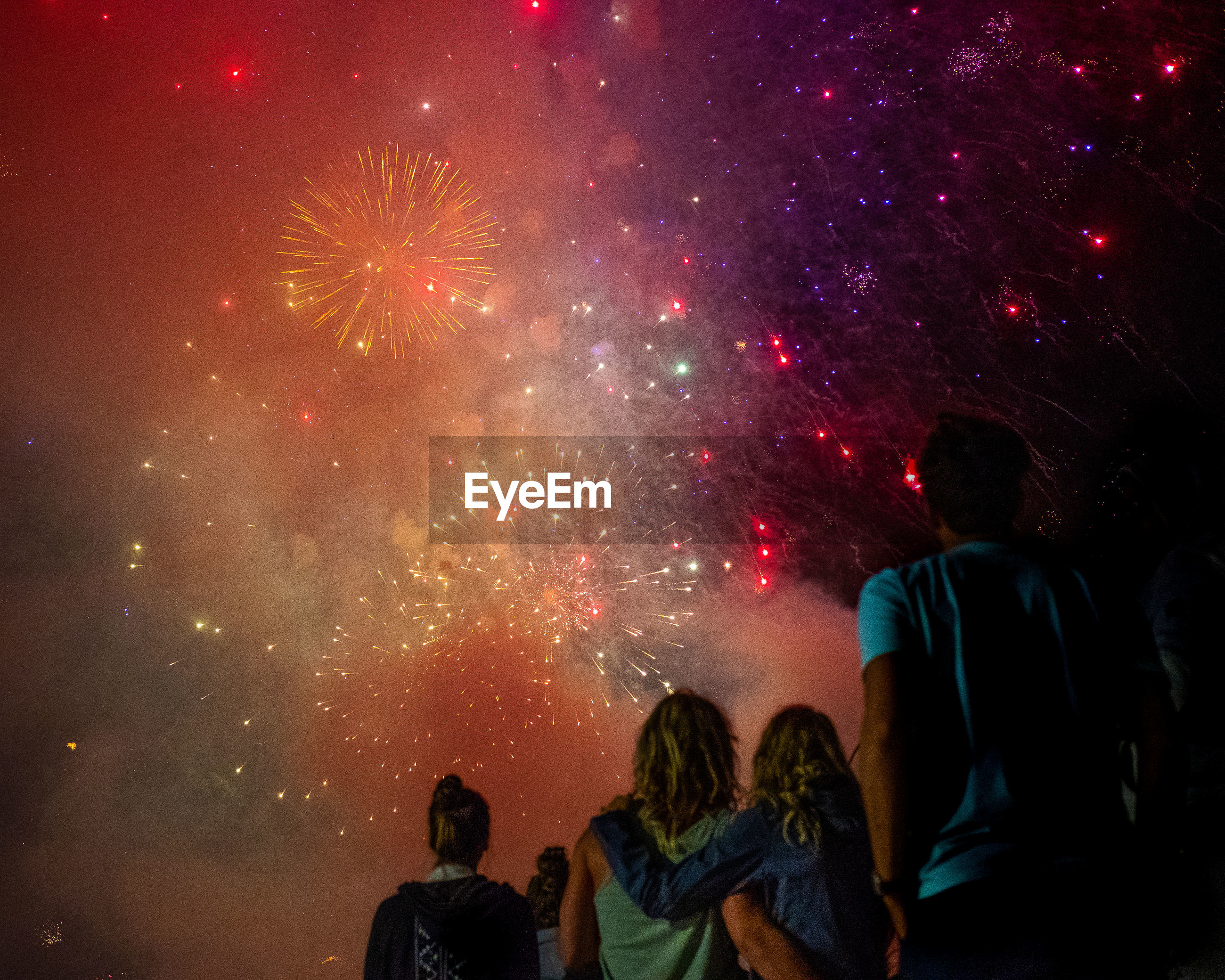 Rear view of people watching firework display in sky at night