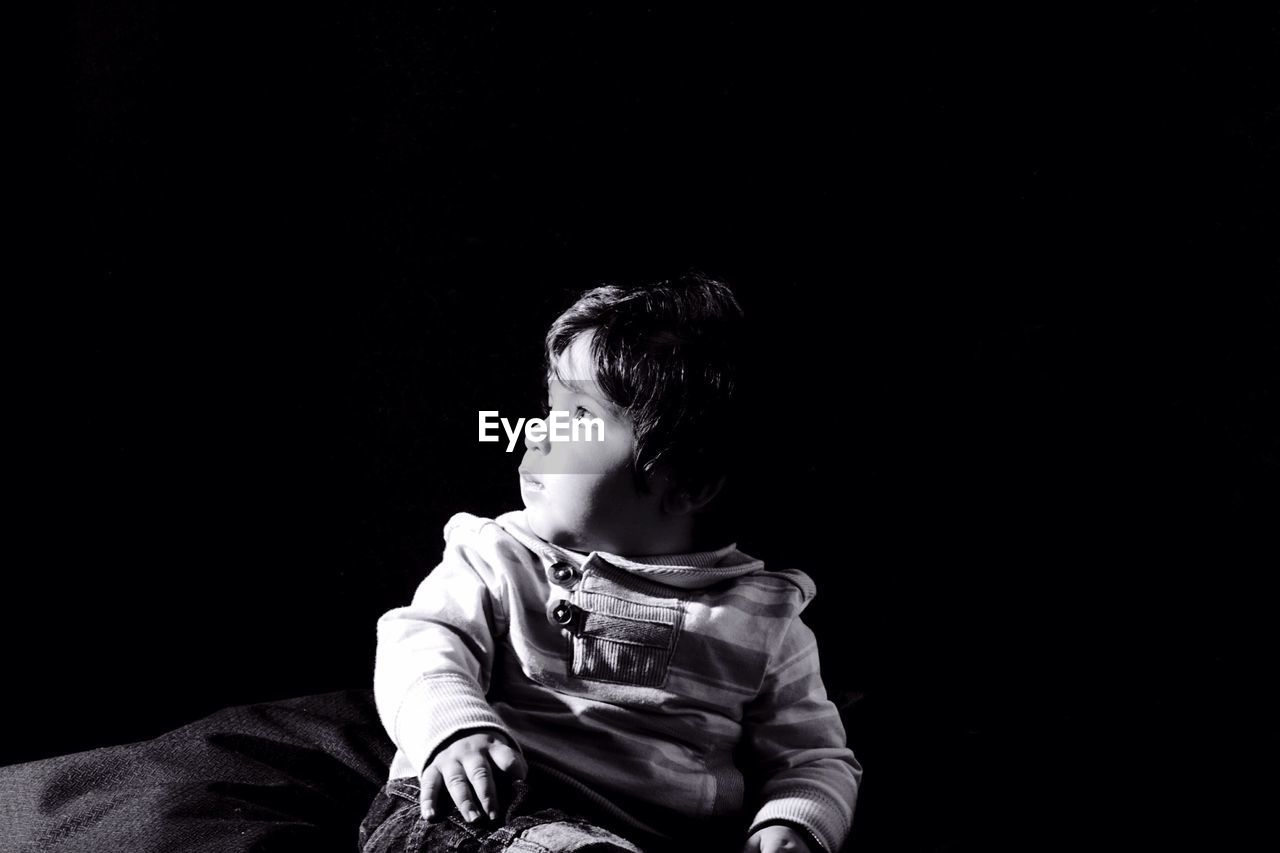 Close-up of cute boy looking away over black background