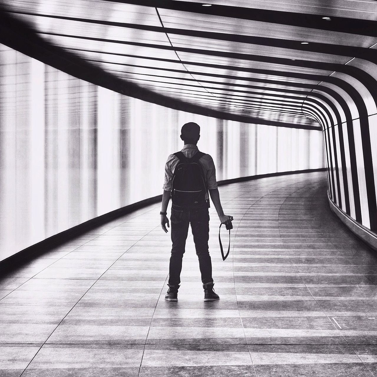 Man with camera in corridor of modern building