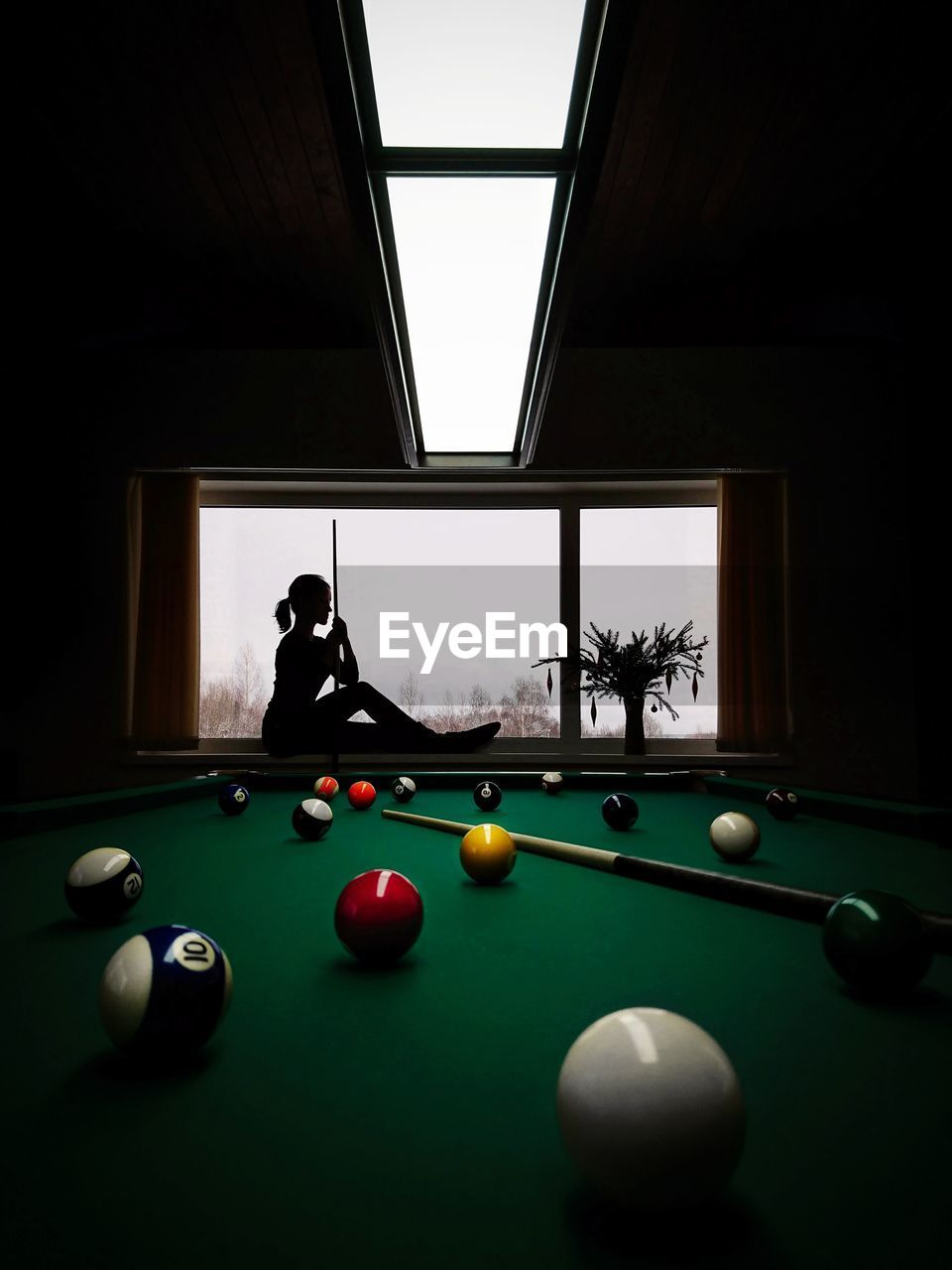 MAN PLAYING WITH BALL ON TABLE IN WINDOW