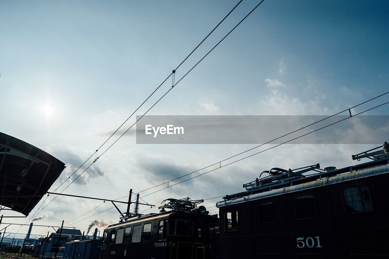 cable, sky, power line, cloud - sky, low angle view, power supply, built structure, day, transportation, mode of transport, outdoors, building exterior, telephone line, no people, architecture, overhead cable car, nature