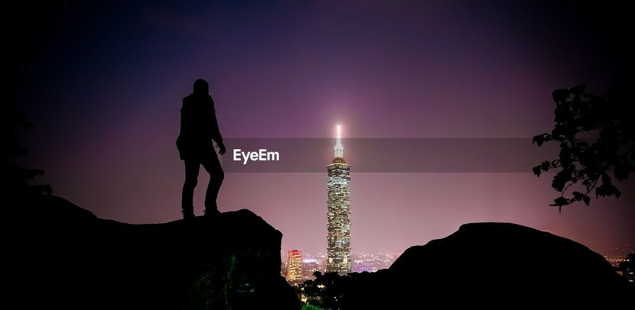 Low angle view of silhouette man standing on rock by illuminated taipei 101 against sky