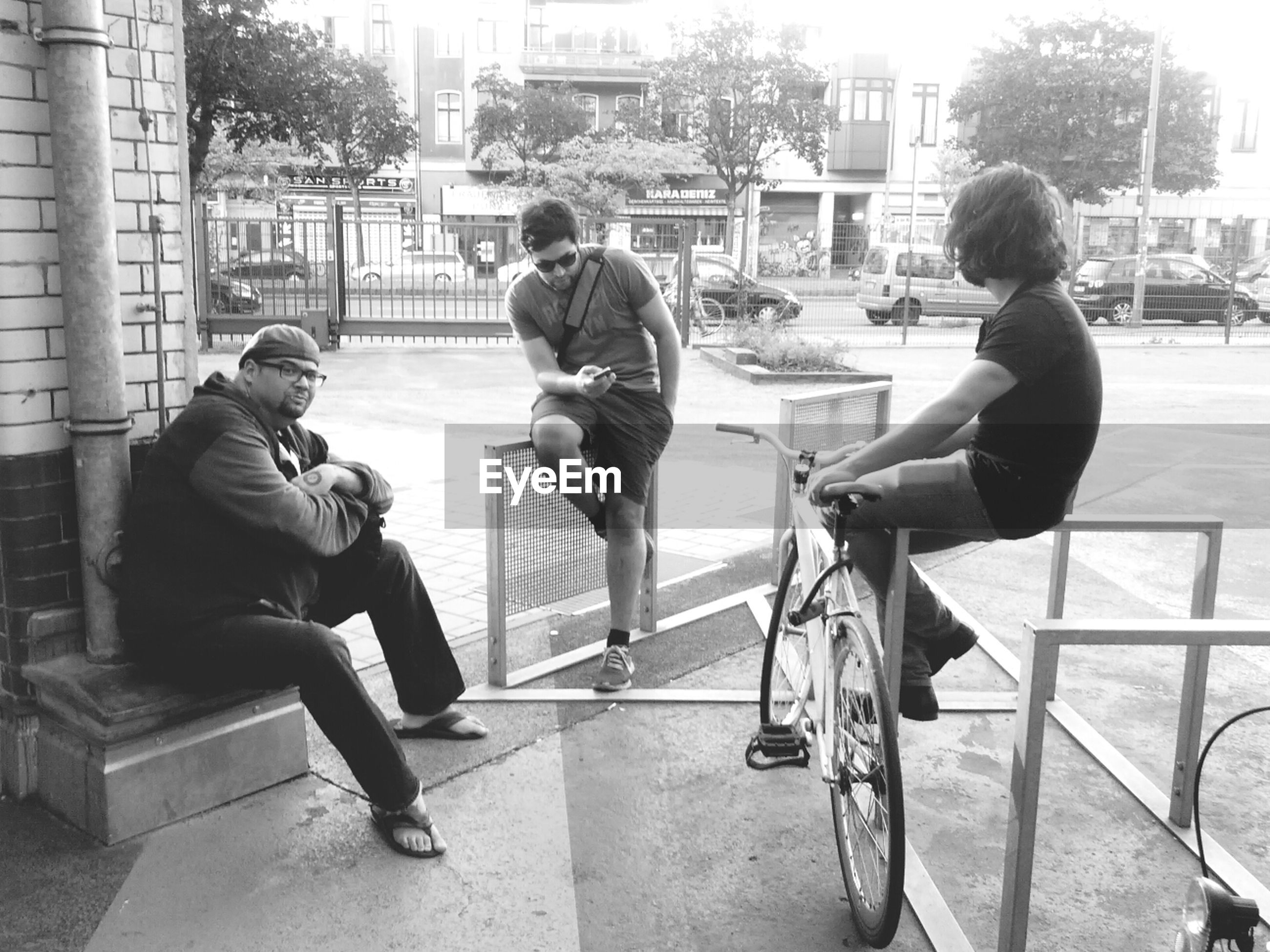 Three young men sitting outdoors
