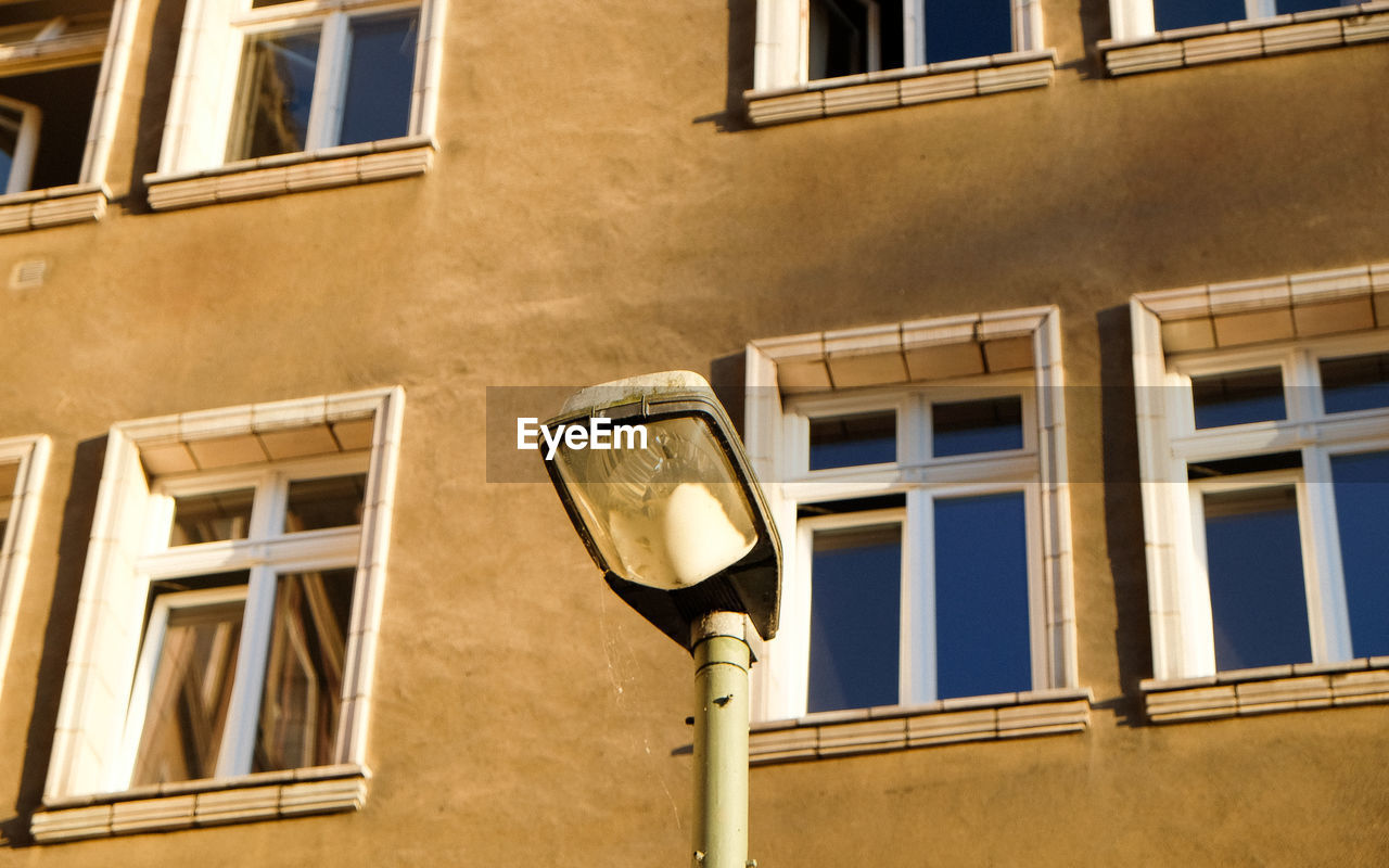 Low angle view of streetlight by building with closed window