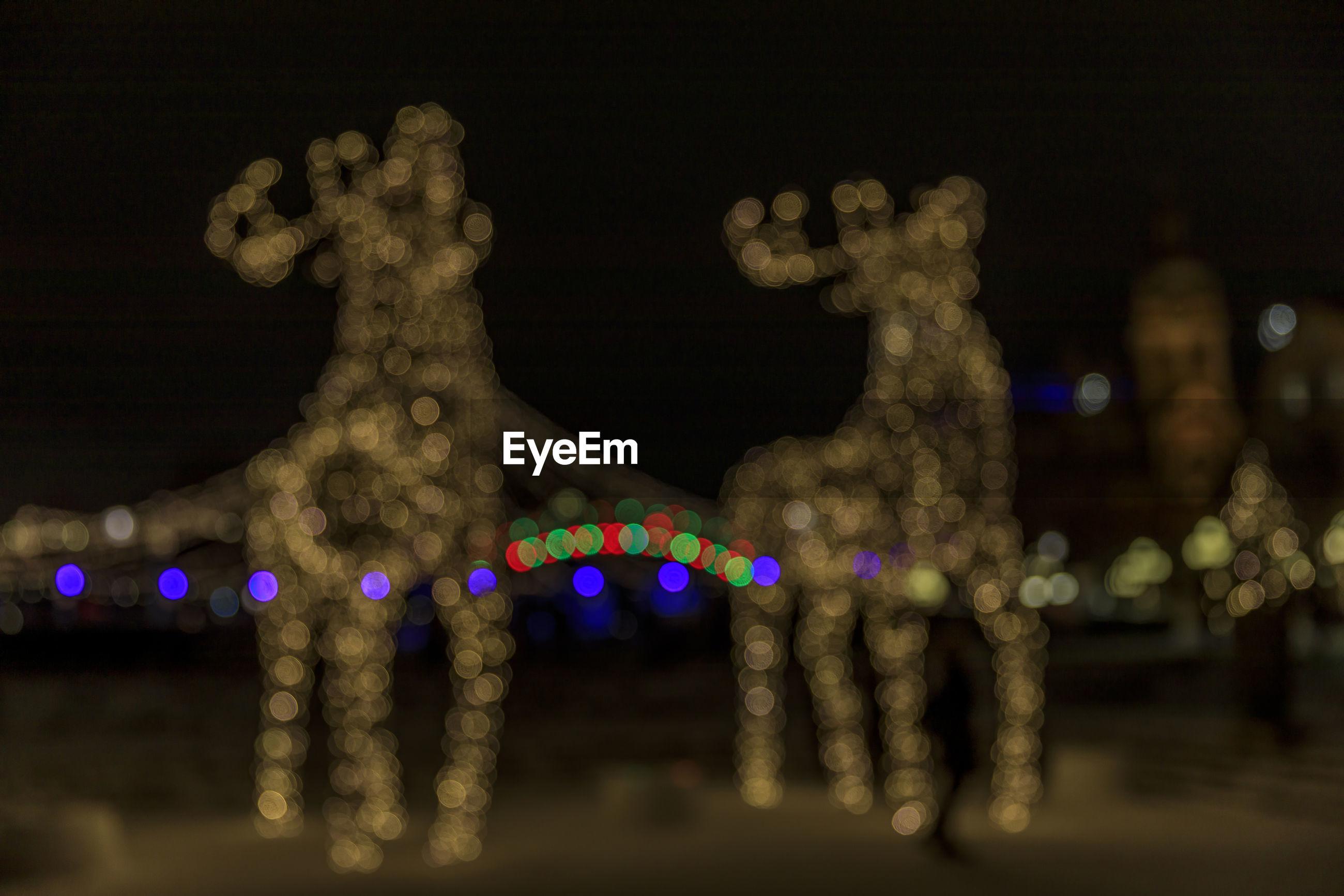 Defocused image of illuminated christmas decorations at night