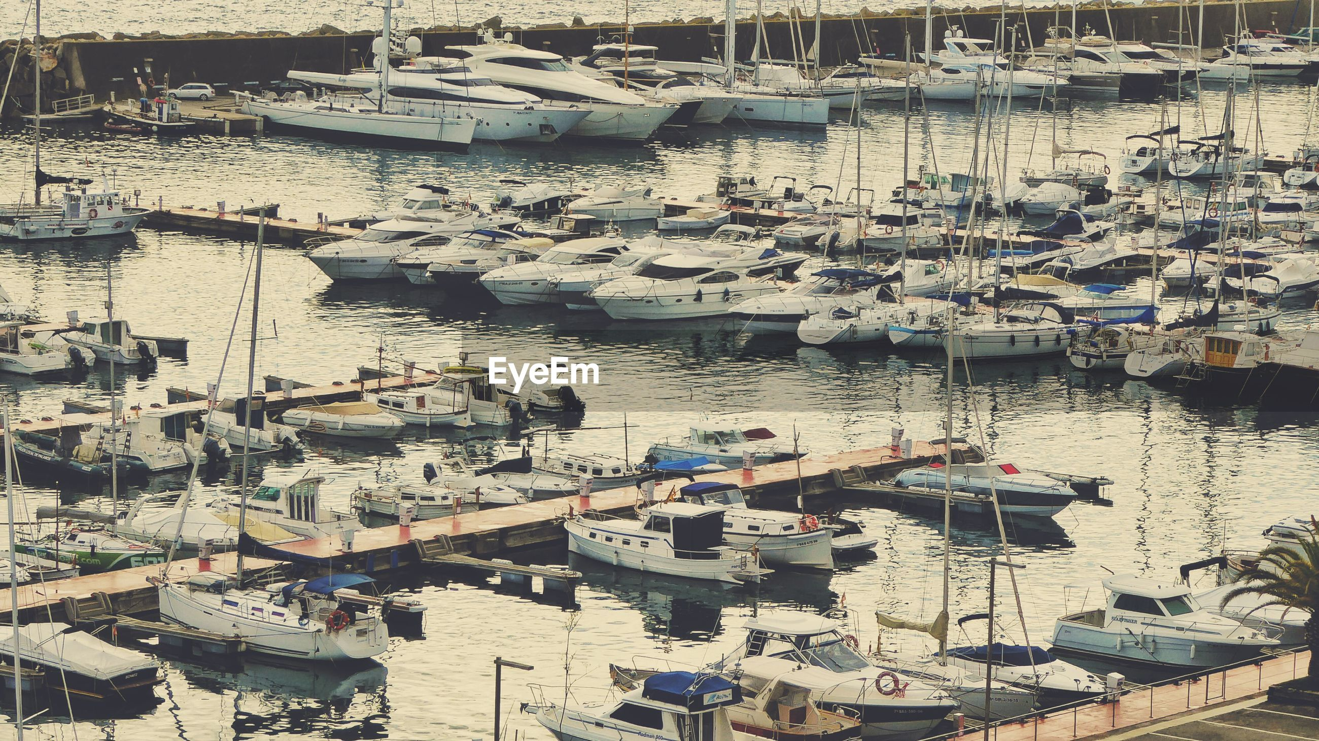 HIGH ANGLE VIEW OF BOATS MOORED IN HARBOR