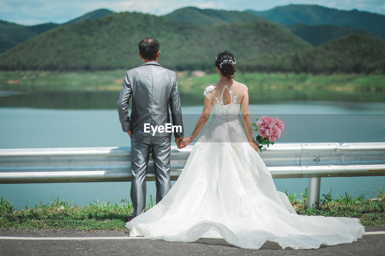 Couple standing against lake
