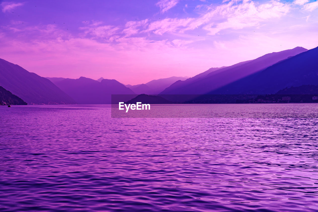 beauty in nature, scenics - nature, water, tranquil scene, waterfront, sky, mountain, tranquility, idyllic, sunset, mountain range, non-urban scene, no people, sea, rippled, cloud - sky, nature, remote, purple