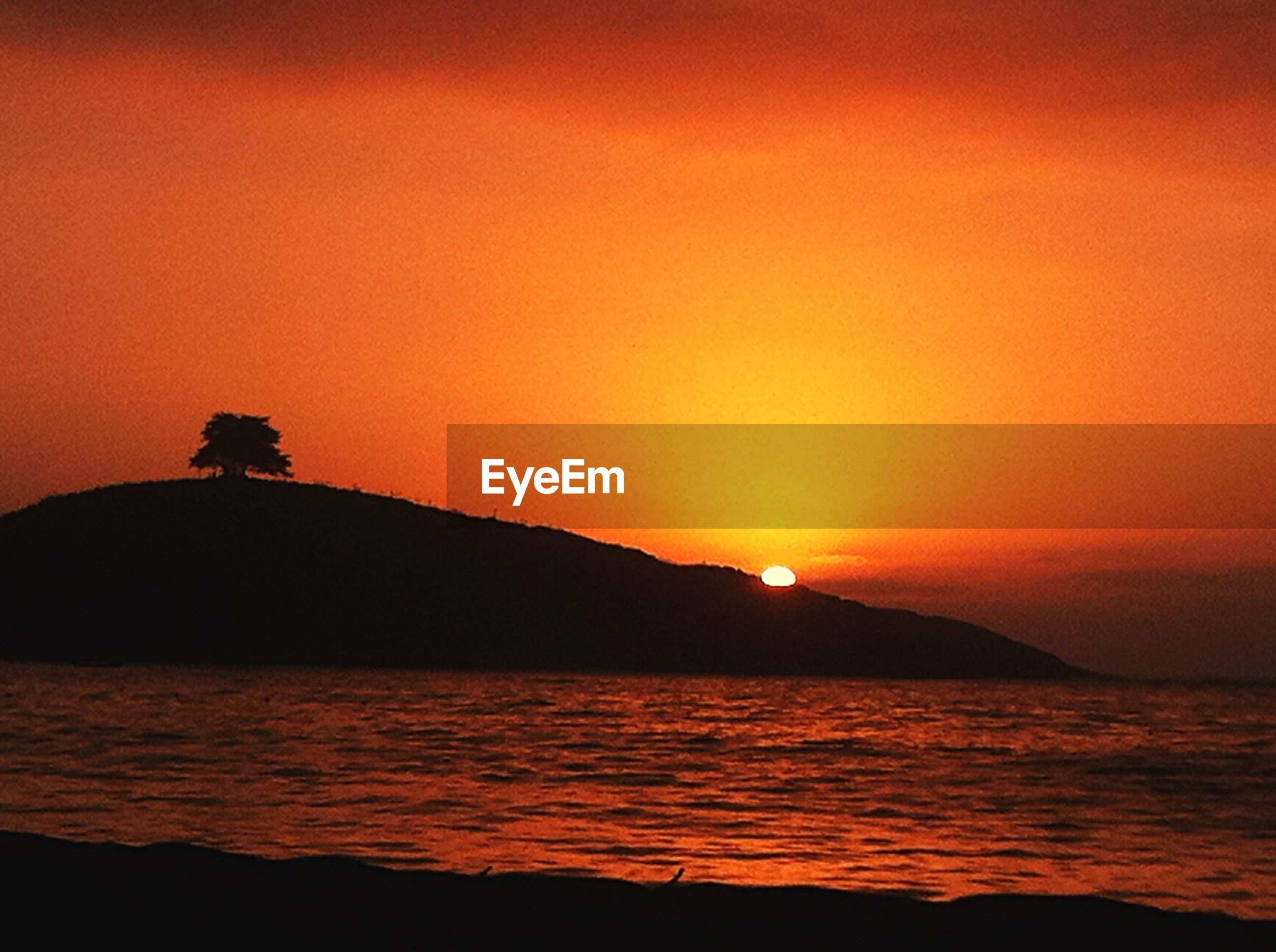 sunset, silhouette, water, sea, orange color, scenics, tranquil scene, beauty in nature, tranquility, sun, idyllic, nature, sky, horizon over water, copy space, mountain, rock - object, waterfront, rippled, clear sky