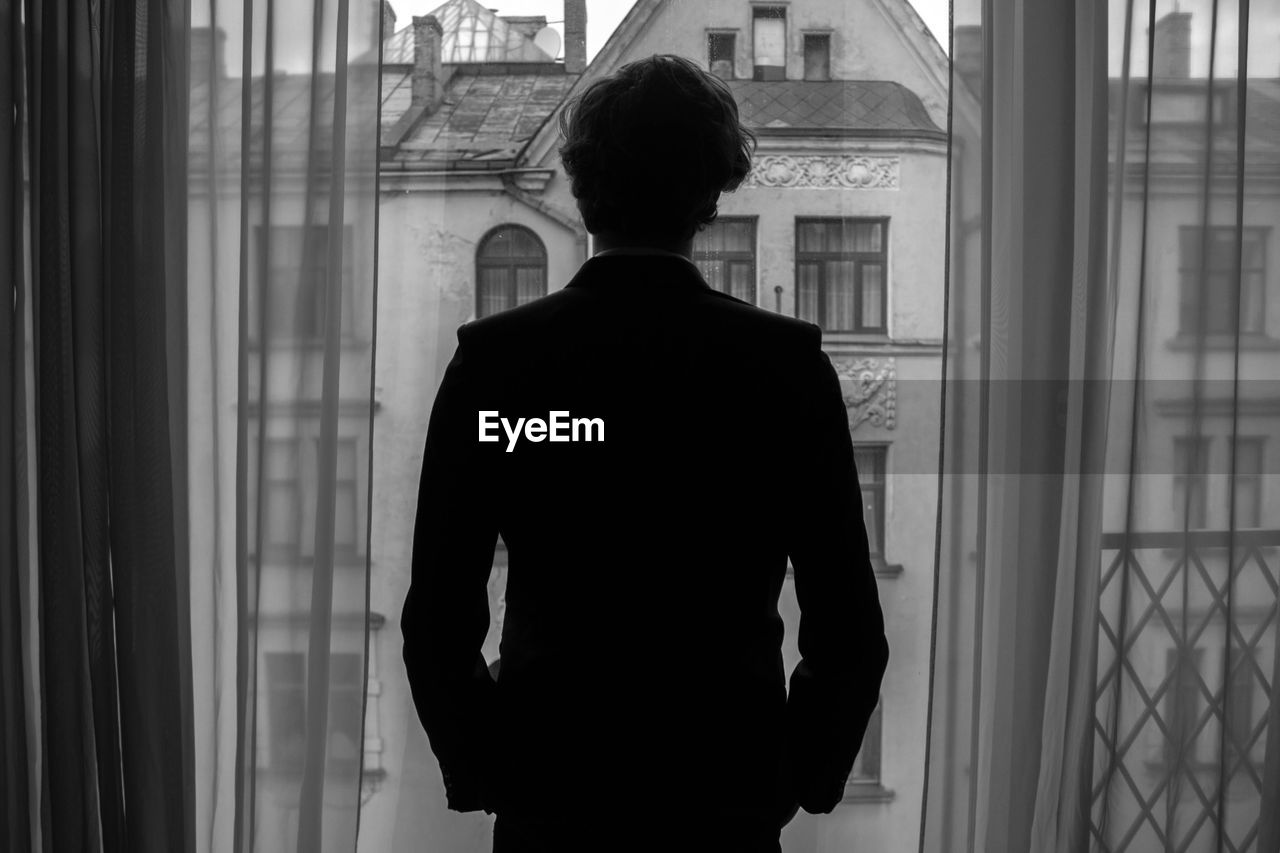 Rear view of man standing on window balcony