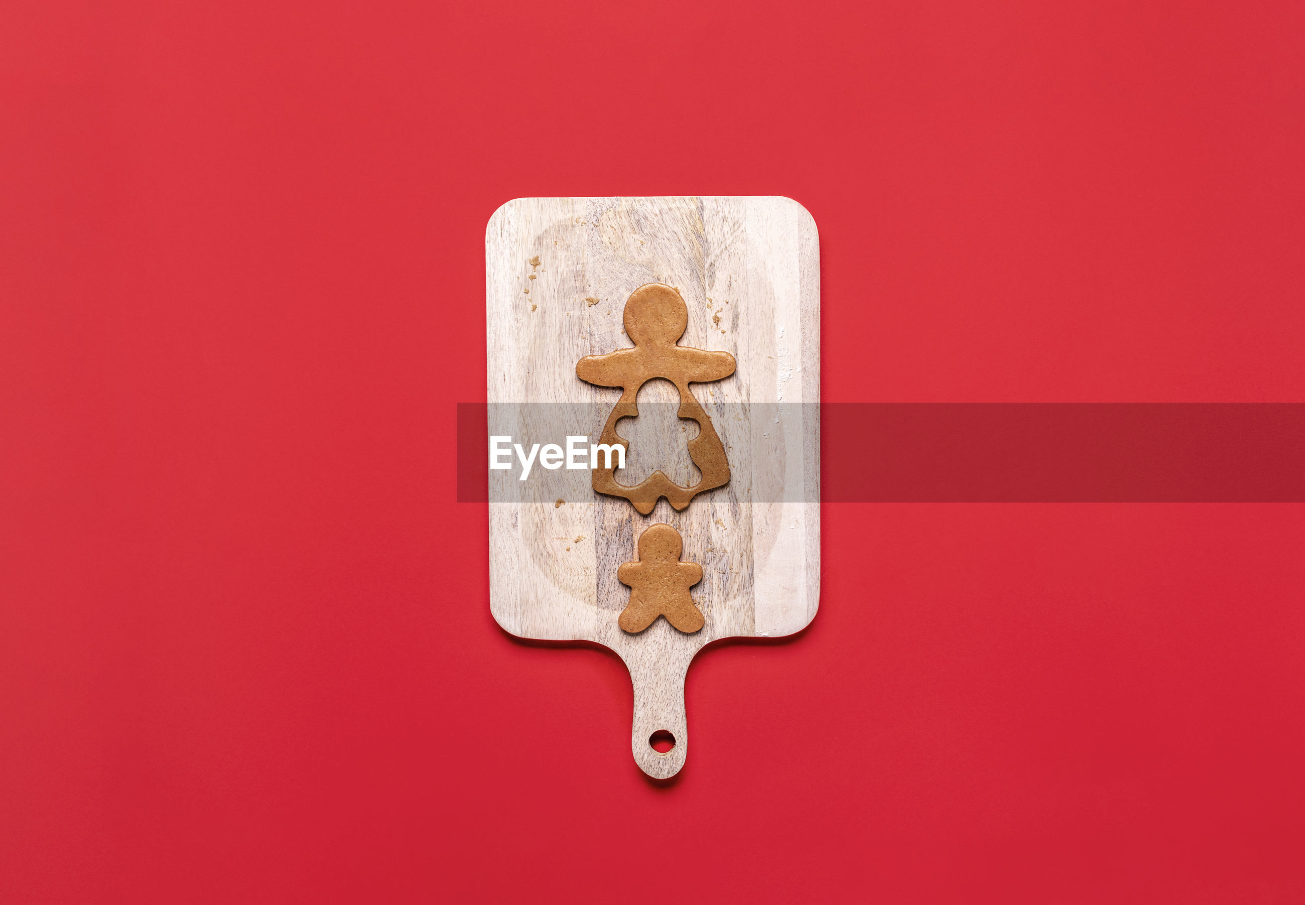 Directly above shot of gingerbread cookie on cutting board over red background