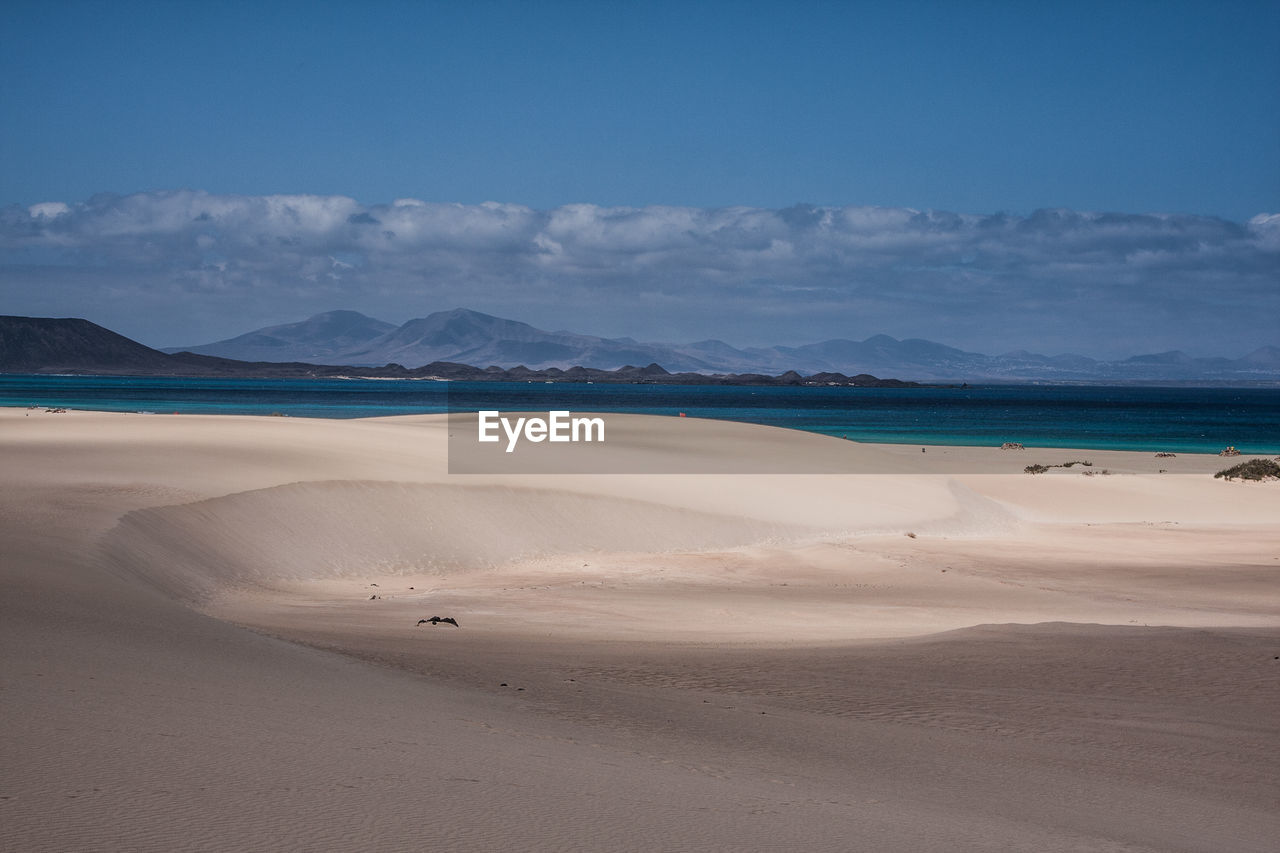 sand, beach, scenics, beauty in nature, sea, nature, tranquility, tranquil scene, shore, sky, water, outdoors, day, cloud - sky, landscape, no people, horizon over water, arid climate, desert, sand dune