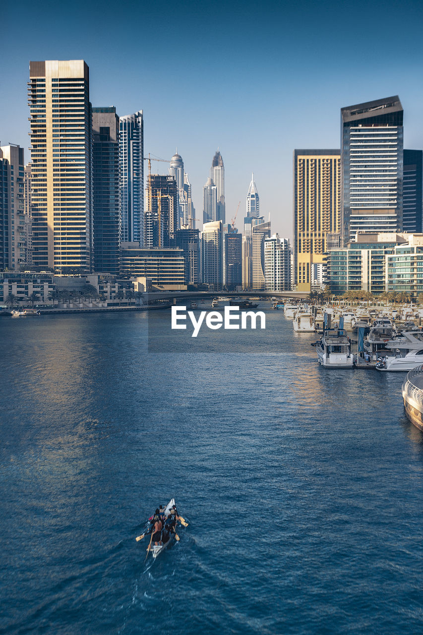 water, building exterior, built structure, architecture, nautical vessel, city, waterfront, office building exterior, sea, sky, skyscraper, nature, real people, transportation, building, men, urban skyline, sport, day, tall - high, cityscape, outdoors, modern