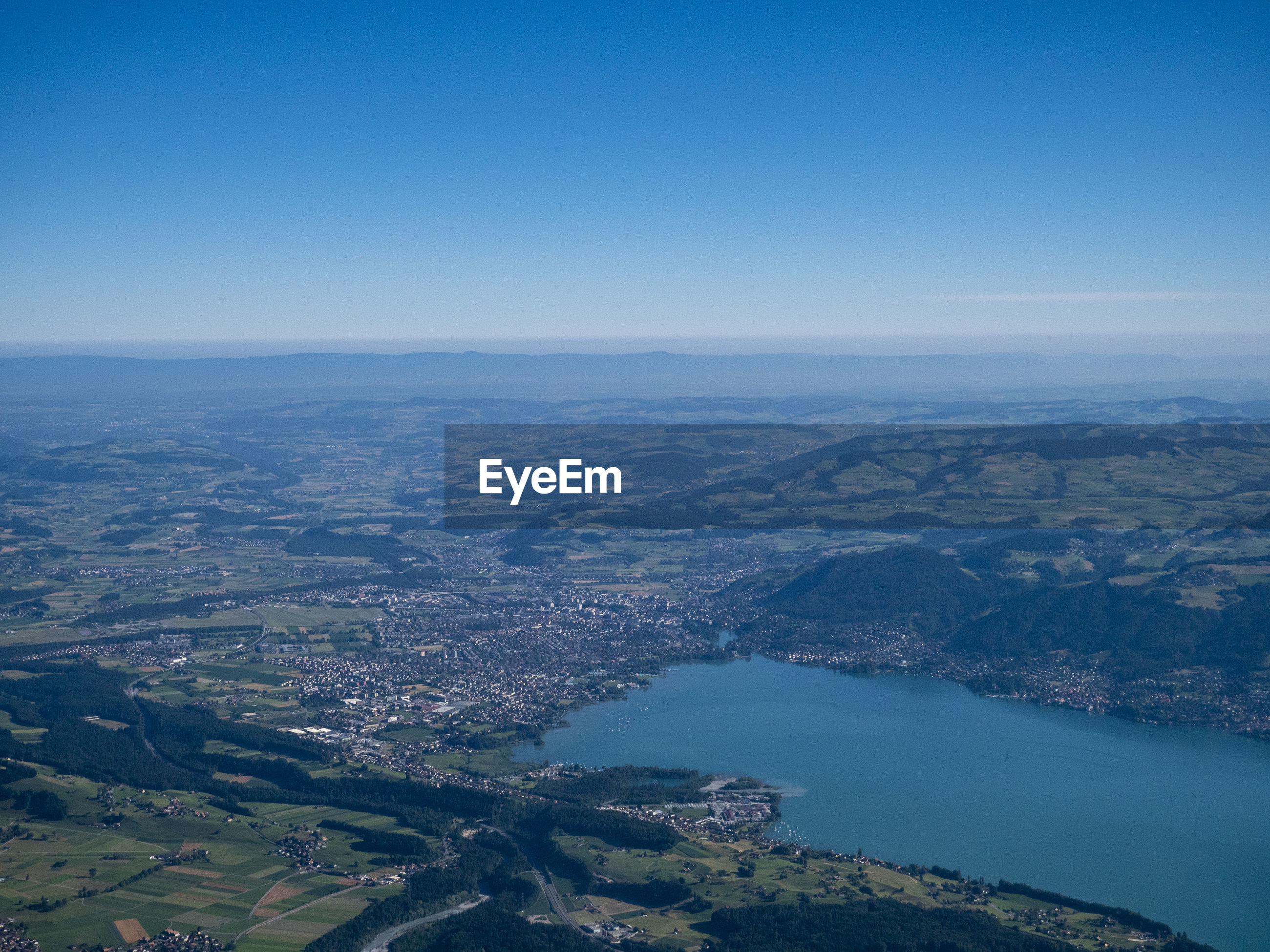 AERIAL VIEW OF SEA AND CITY AGAINST CLEAR SKY
