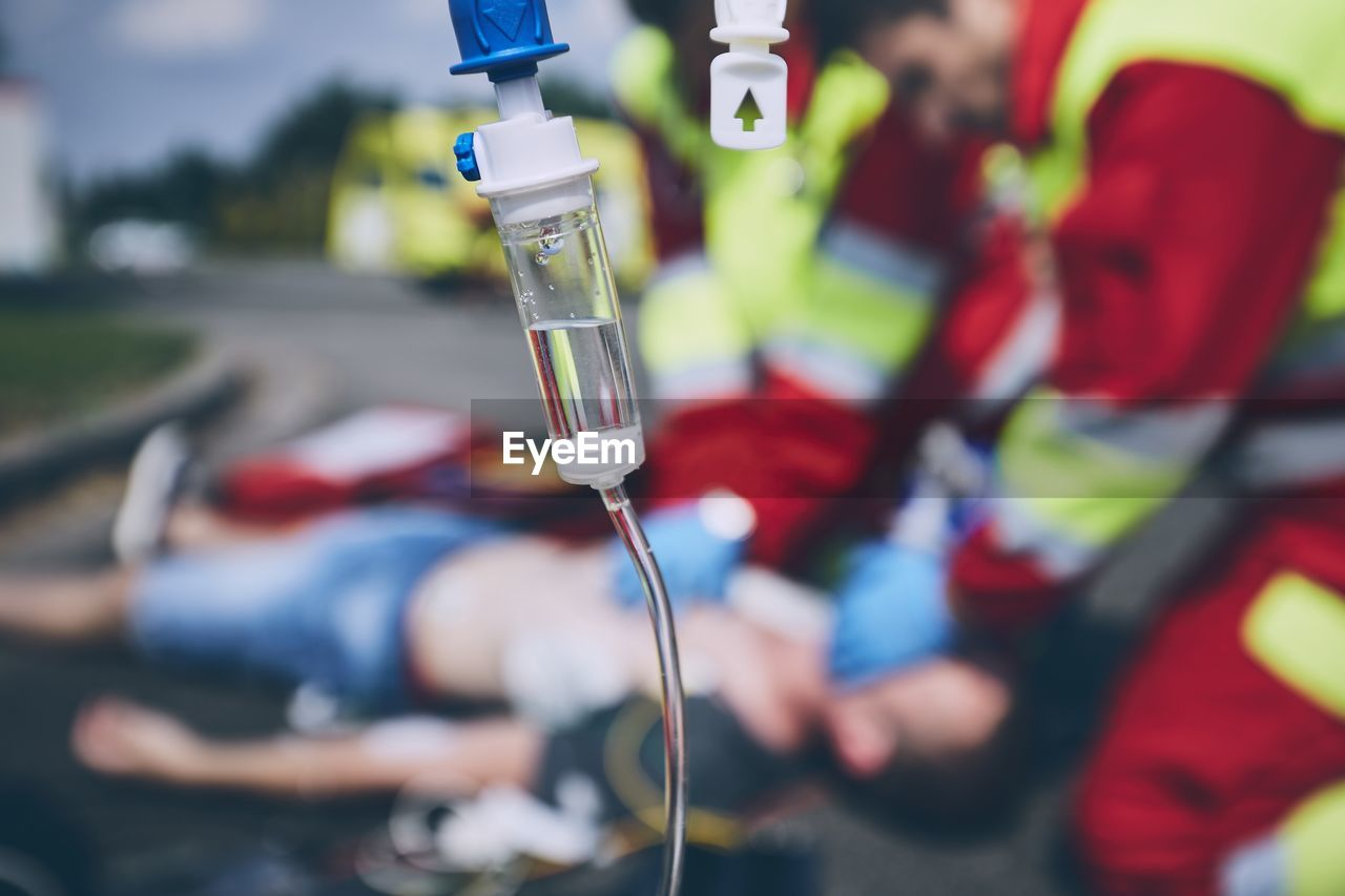 Close-Up Of Iv Drip Against Paramedic Giving Cpr To Unconscious Man Lying On Street