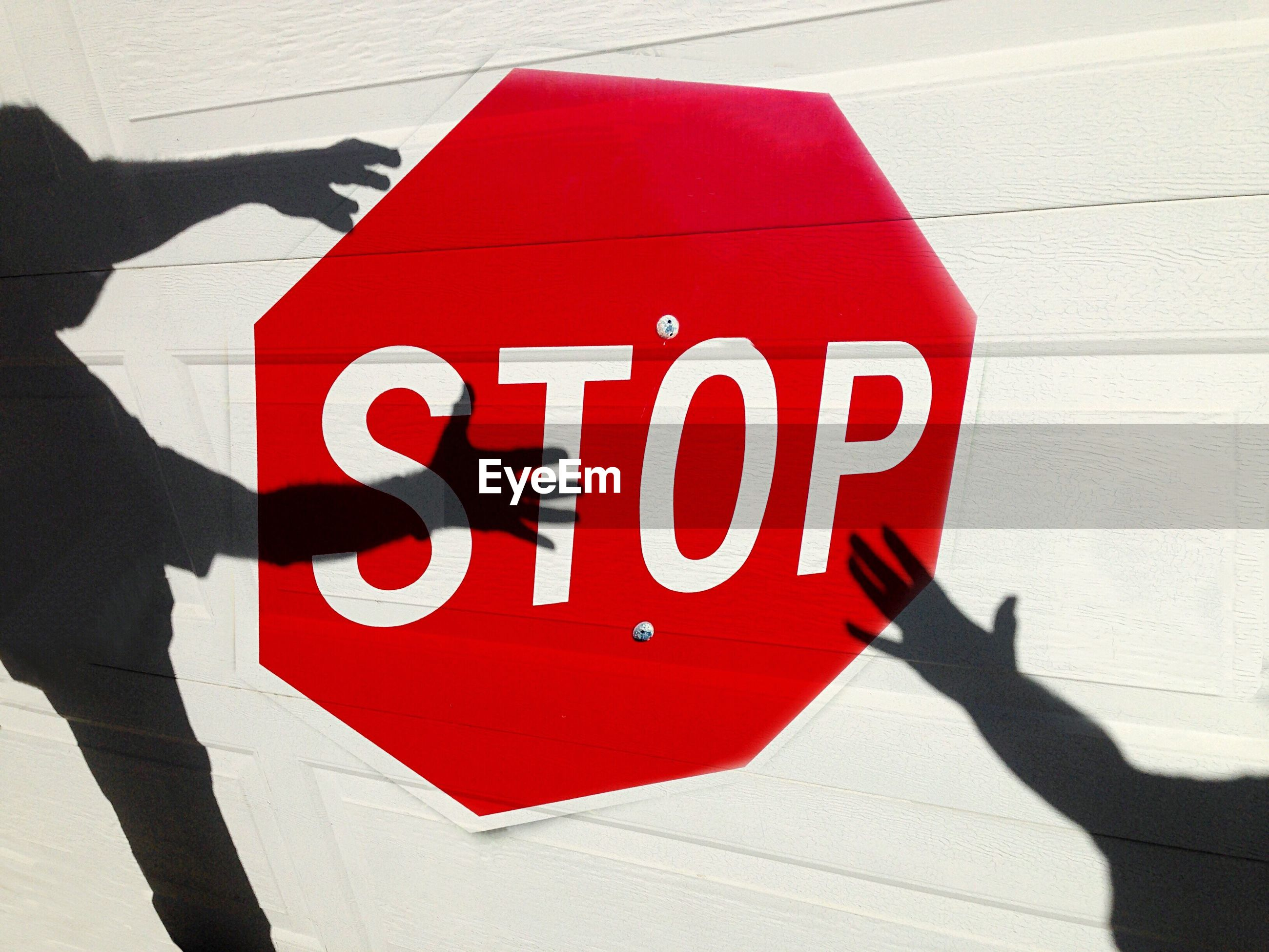 Optical illusion of shadows holding stop sign painted on white wall