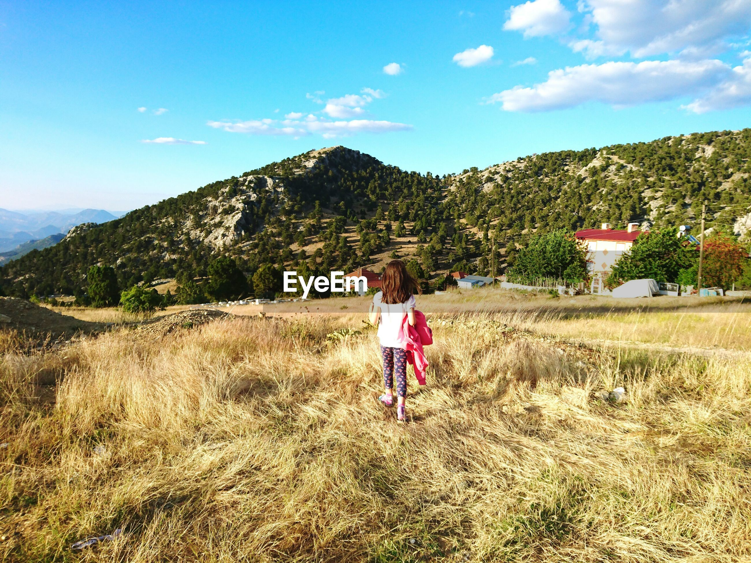 Full Length Rear View Of Girl Standing On Landscape Against Sky
