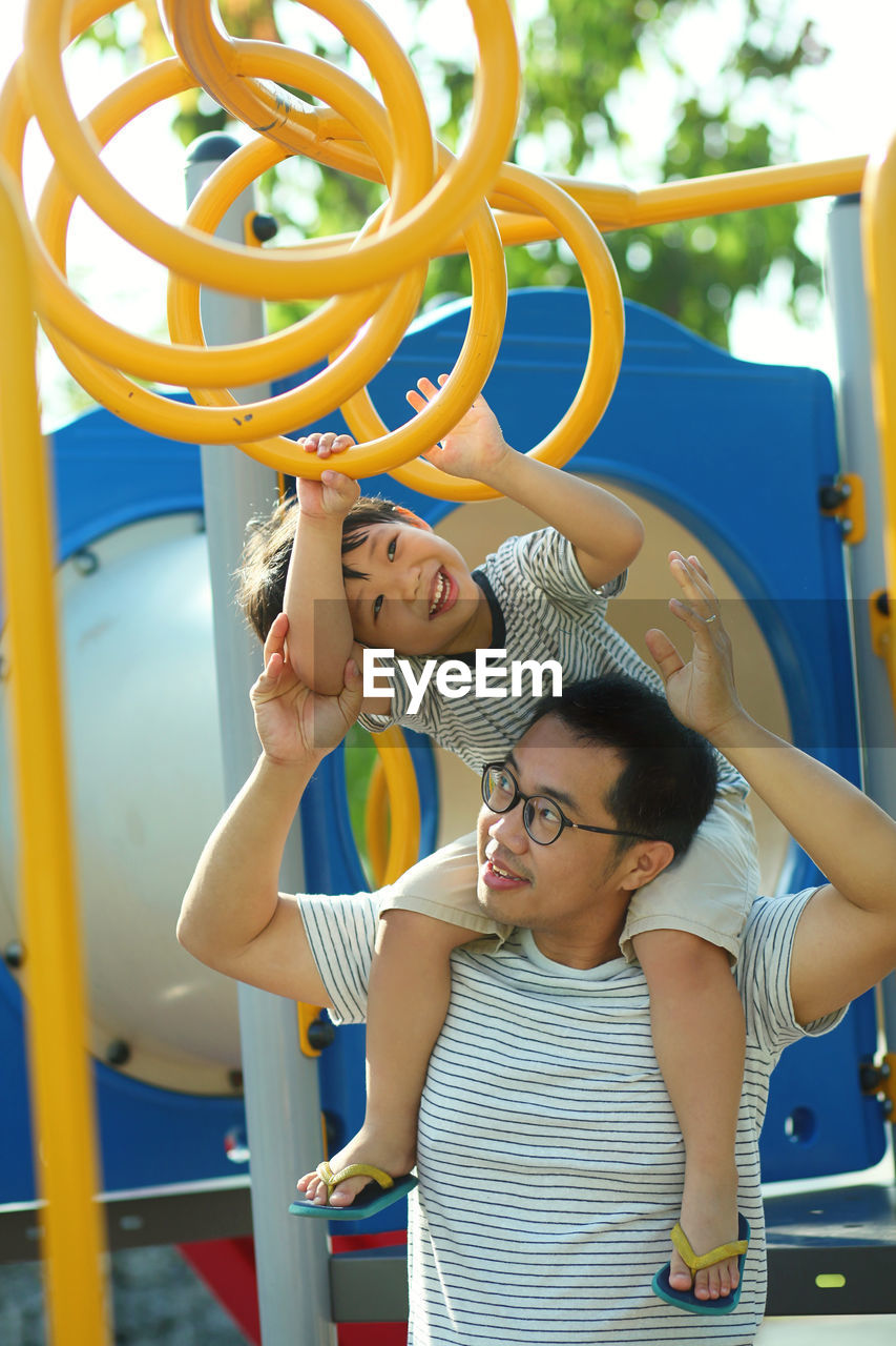 Father assisting son in climbing jungle gym standing on playground