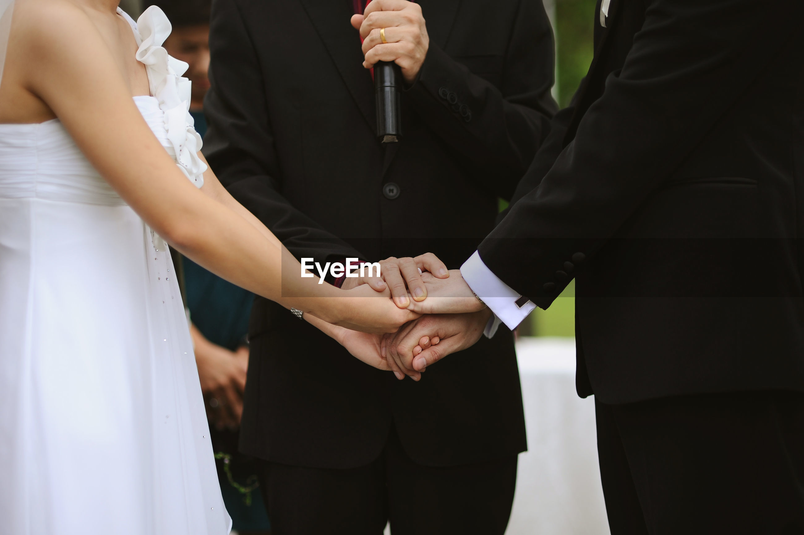 Midsection of priest holding hands of couple during weeding