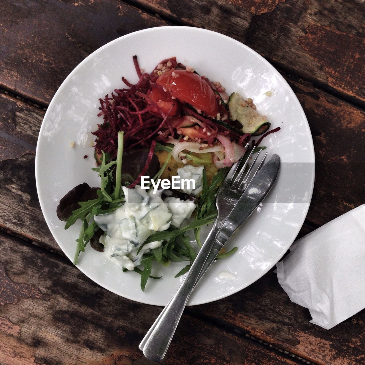 High Angle View Of Salad With Fork And Knife In Plate On Wooden Table