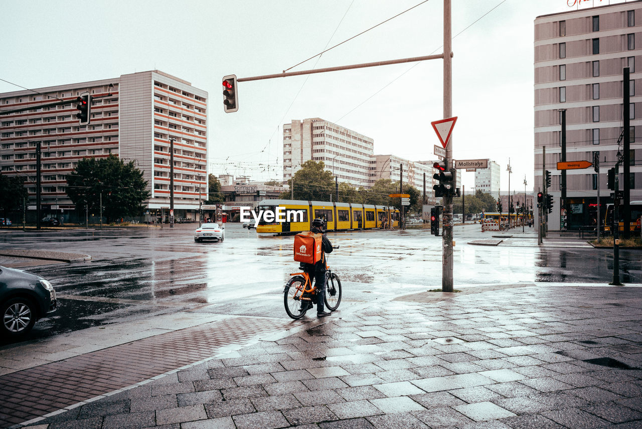 architecture, city, building exterior, transportation, street, built structure, mode of transportation, bicycle, land vehicle, real people, city life, city street, building, one person, car, sky, motor vehicle, road, day, nature, outdoors, riding, rain