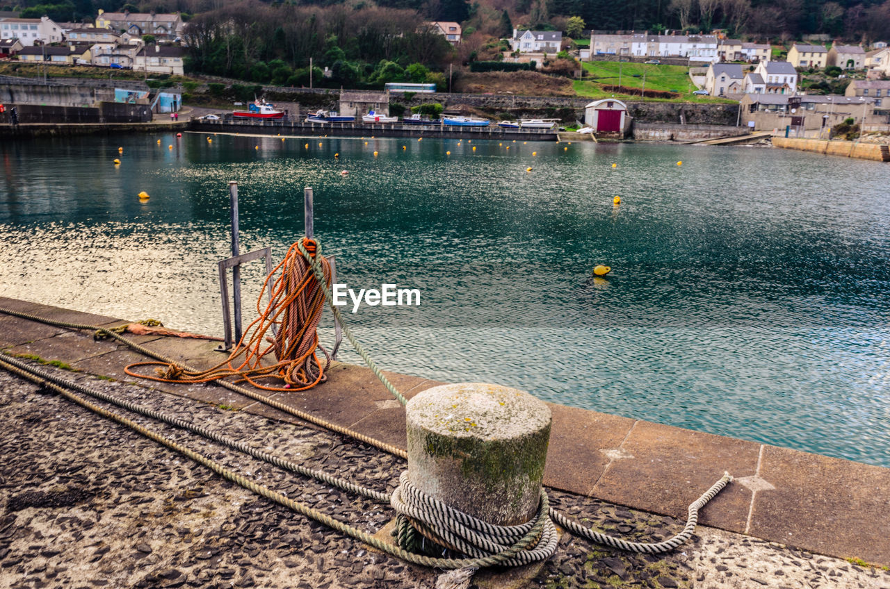 water, nautical vessel, built structure, day, fishing net, architecture, mode of transport, outdoors, transportation, high angle view, building exterior, harbor, moored, lake, no people