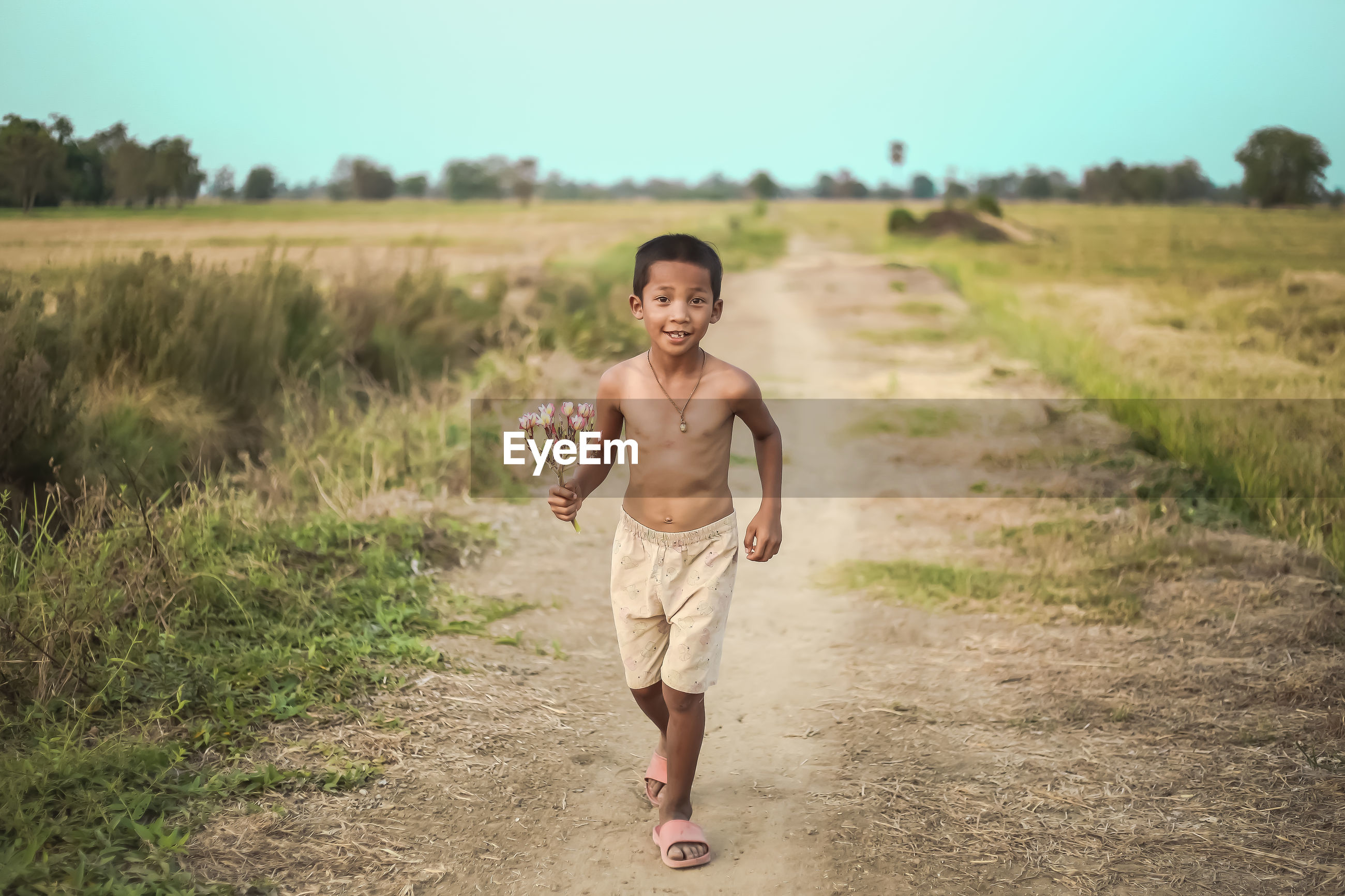 Portrait of boy with flowers running on dirt road against clear sky