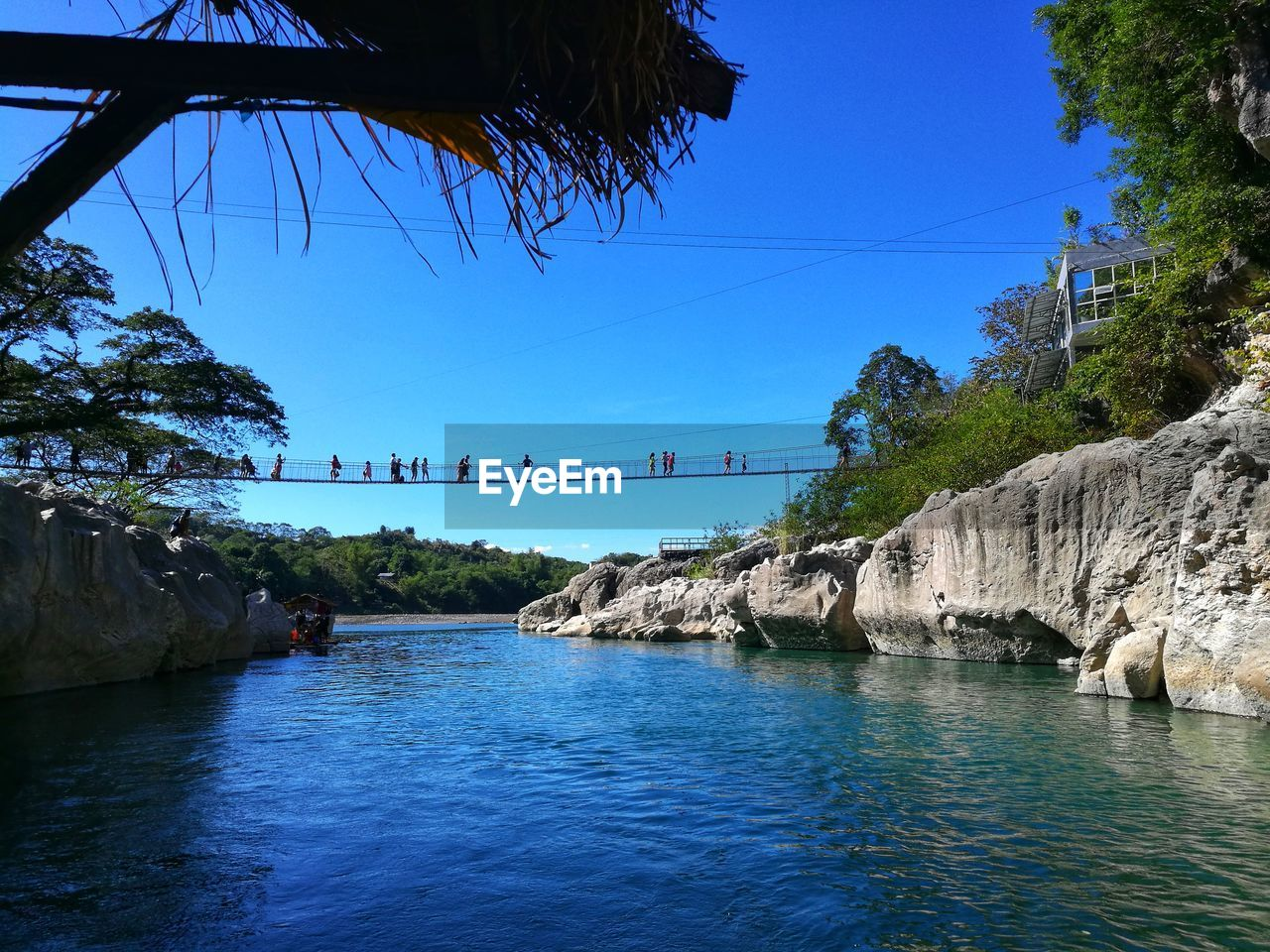 water, sky, tree, nature, waterfront, architecture, day, plant, connection, built structure, bridge, scenics - nature, blue, rock, beauty in nature, river, rock - object, tranquility, bridge - man made structure, no people, outdoors, flowing water