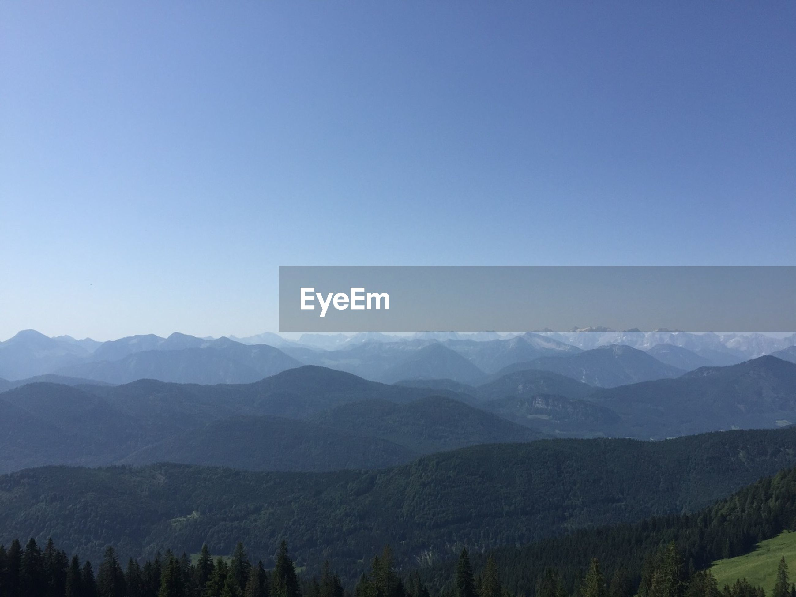View of tree mountains against clear sky at lenggries