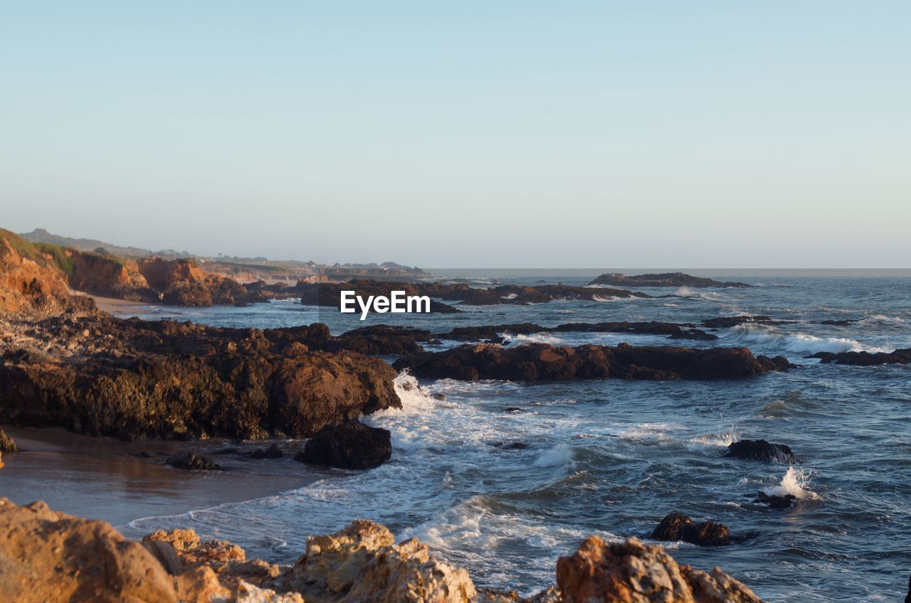 water, sky, sea, beauty in nature, rock, scenics - nature, clear sky, rock - object, motion, copy space, solid, nature, beach, land, wave, no people, horizon, tranquility, tranquil scene, horizon over water, outdoors, power in nature, rocky coastline, marine