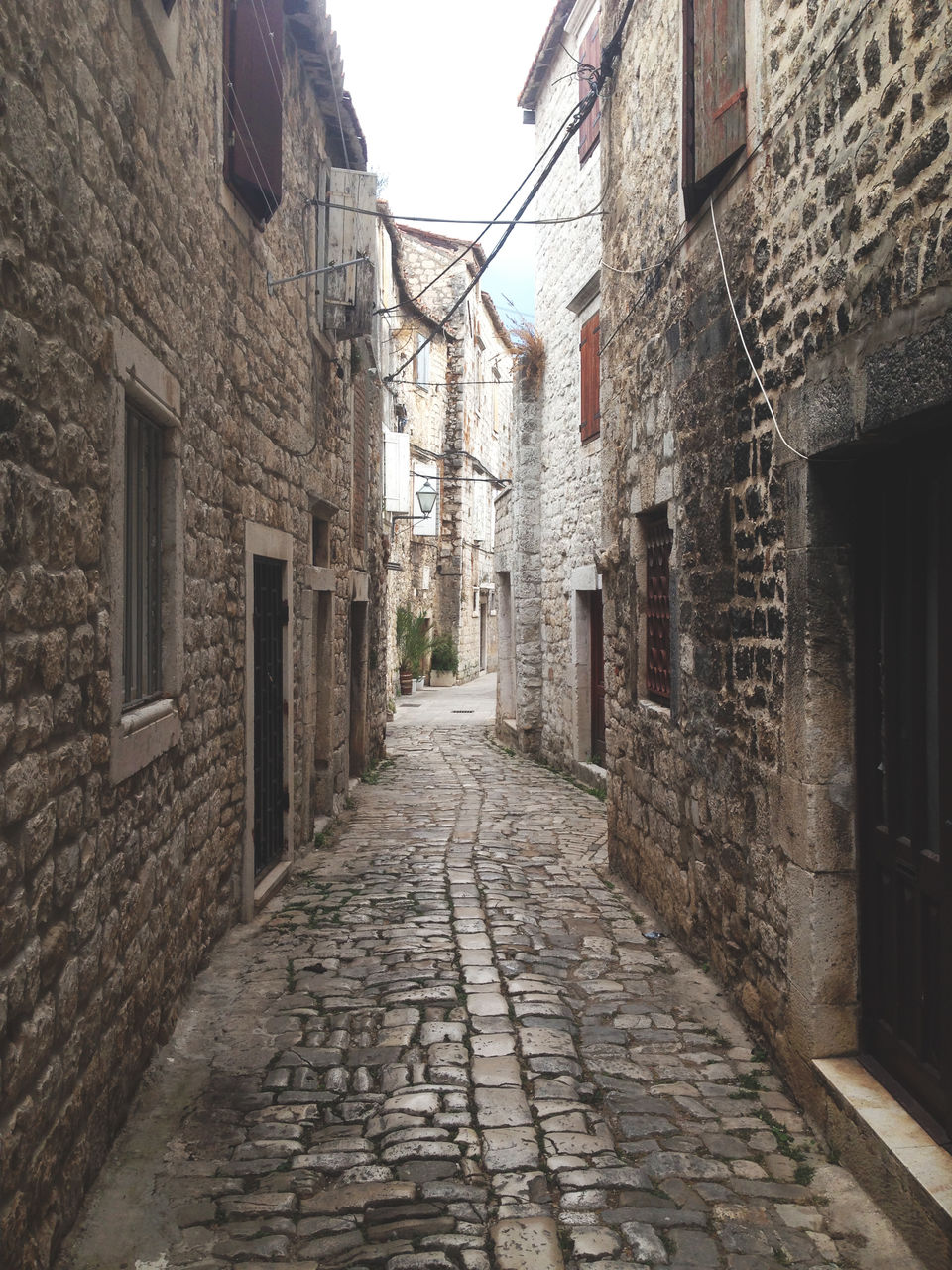 architecture, building exterior, built structure, building, street, direction, residential district, the way forward, city, narrow, cobblestone, no people, footpath, day, alley, house, wall, town, old, outdoors, long, paving stone